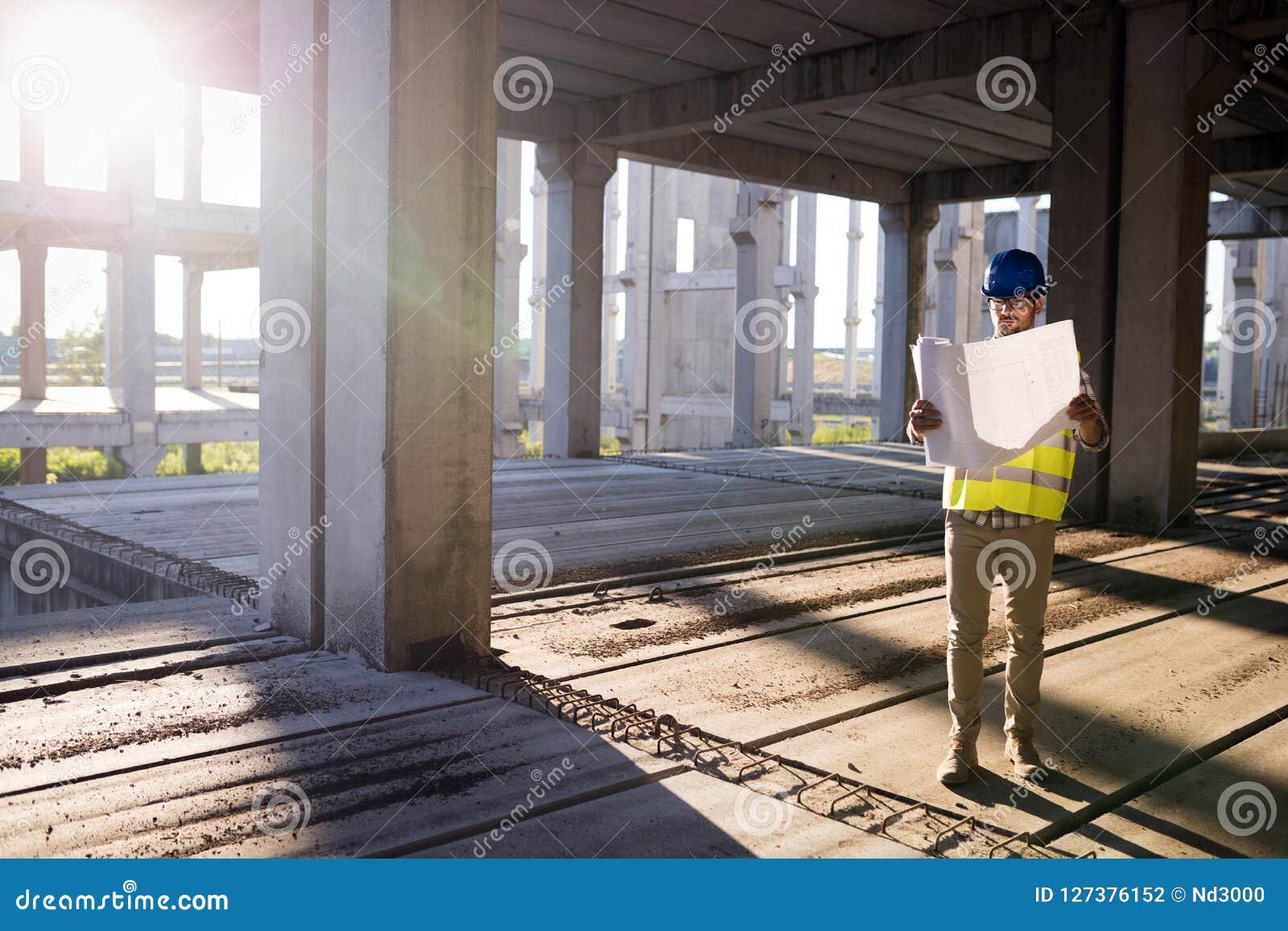 Инженеры работая на строительной площадке