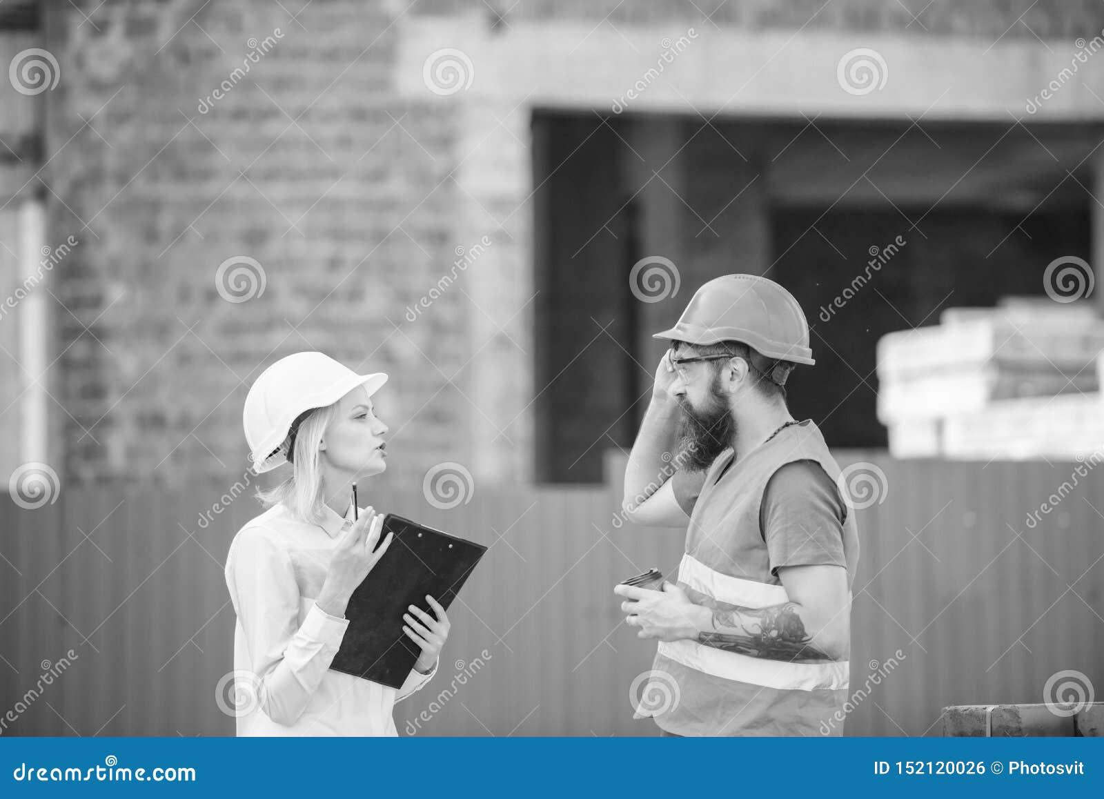 Инженер женщины и бородатый зверский построитель обсудить прогресс конструкции Концепция строительной промышленности Отношения