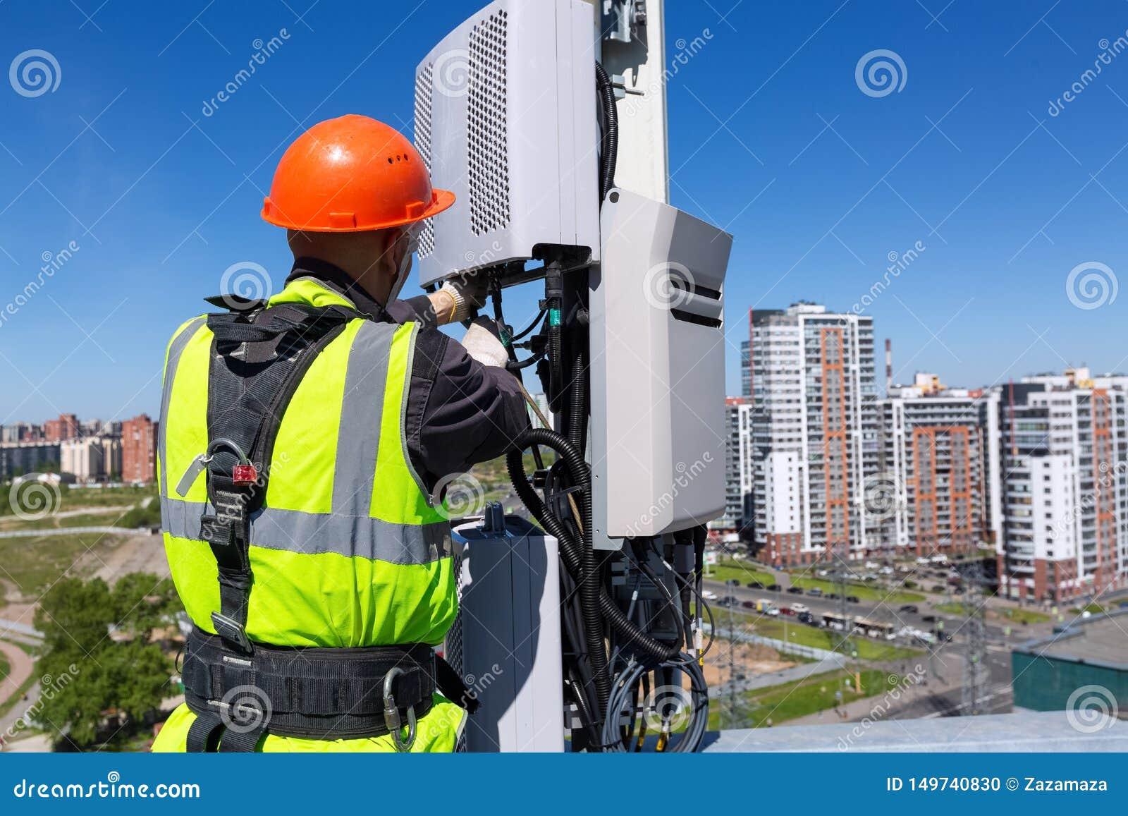 Инженер радиосвязи в шлеме и форме устанавливает оборудование telecomunication в его руку и антенны DCS GSM