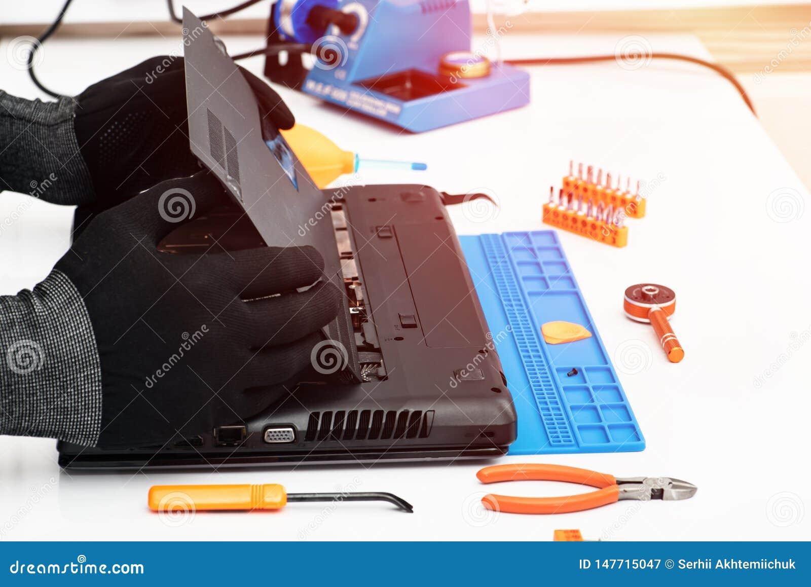 Инженер разбирает детали сломленного ноутбука для ремонта