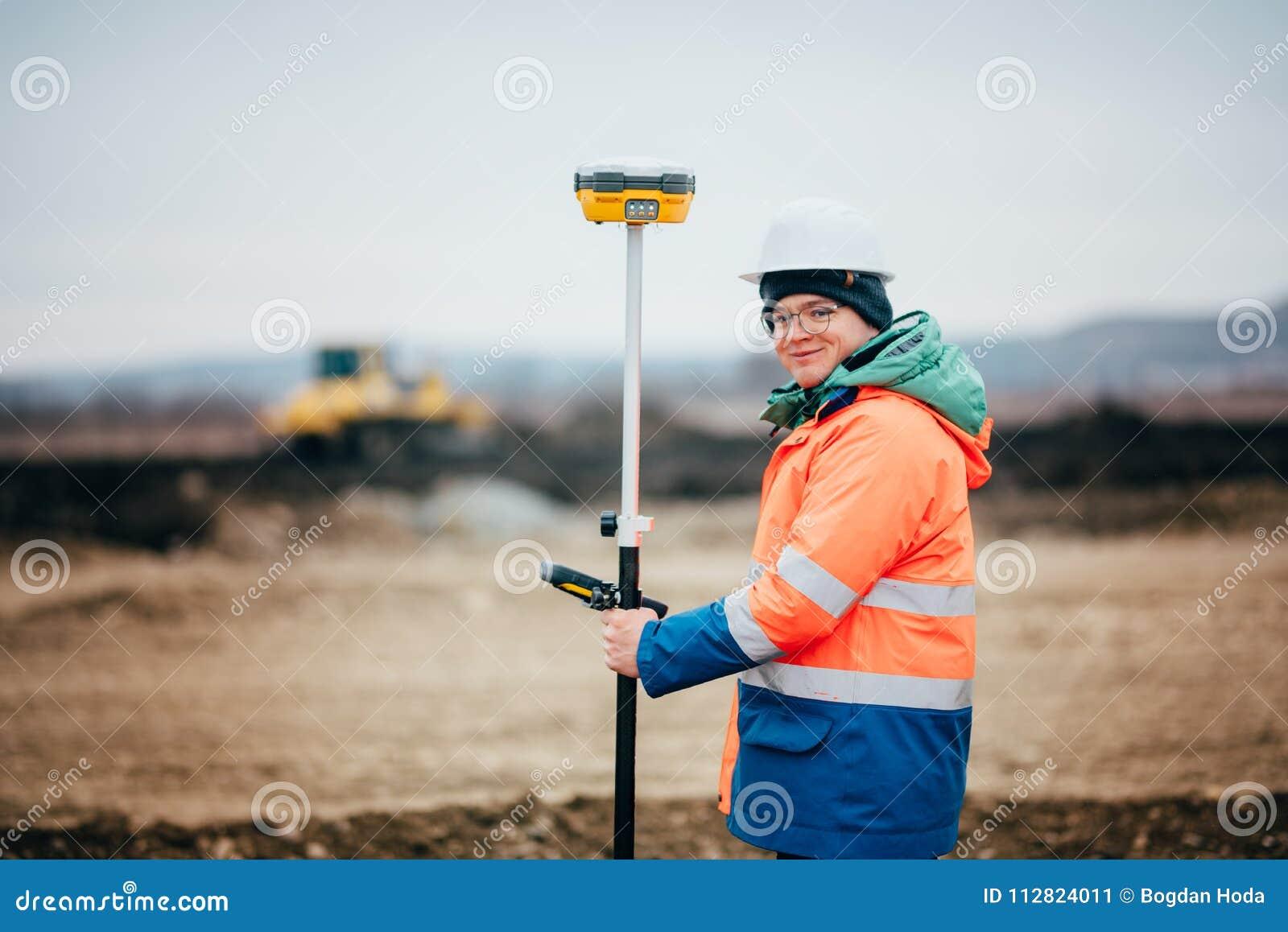 Инженер съемщика работая на строительной площадке шоссе, работающ с теодолитом и системой gps