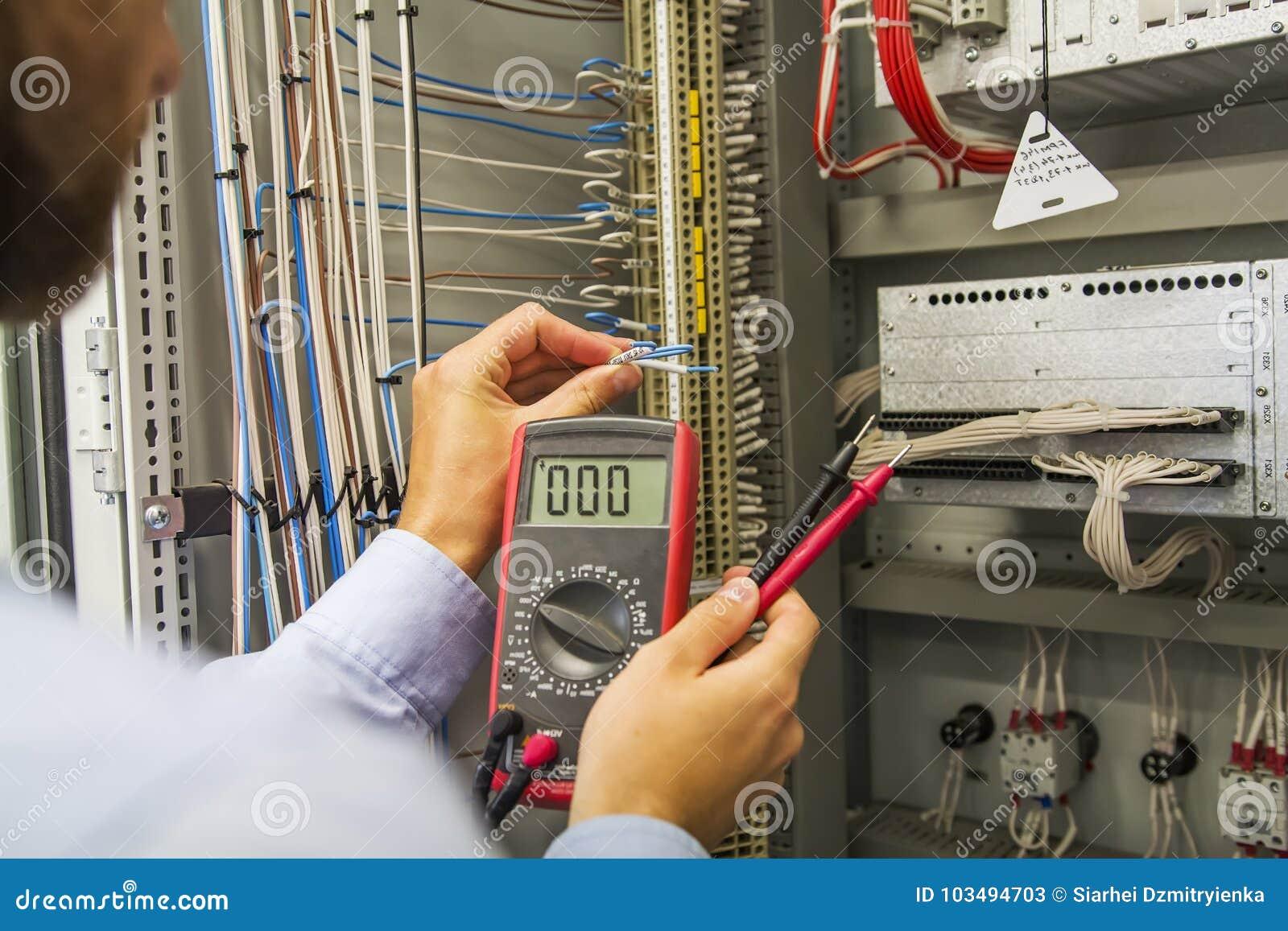Инженер электрика с вольтамперомметром испытывает щиток управления системой электропитания оборудования автоматизации Специалист