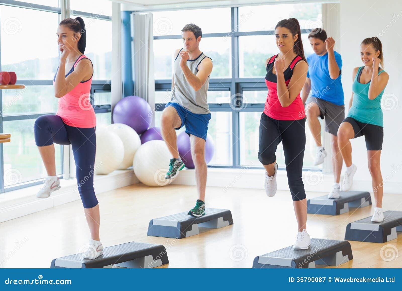 Инструктор при класс фитнеса выполняя тренировку аэробики шага