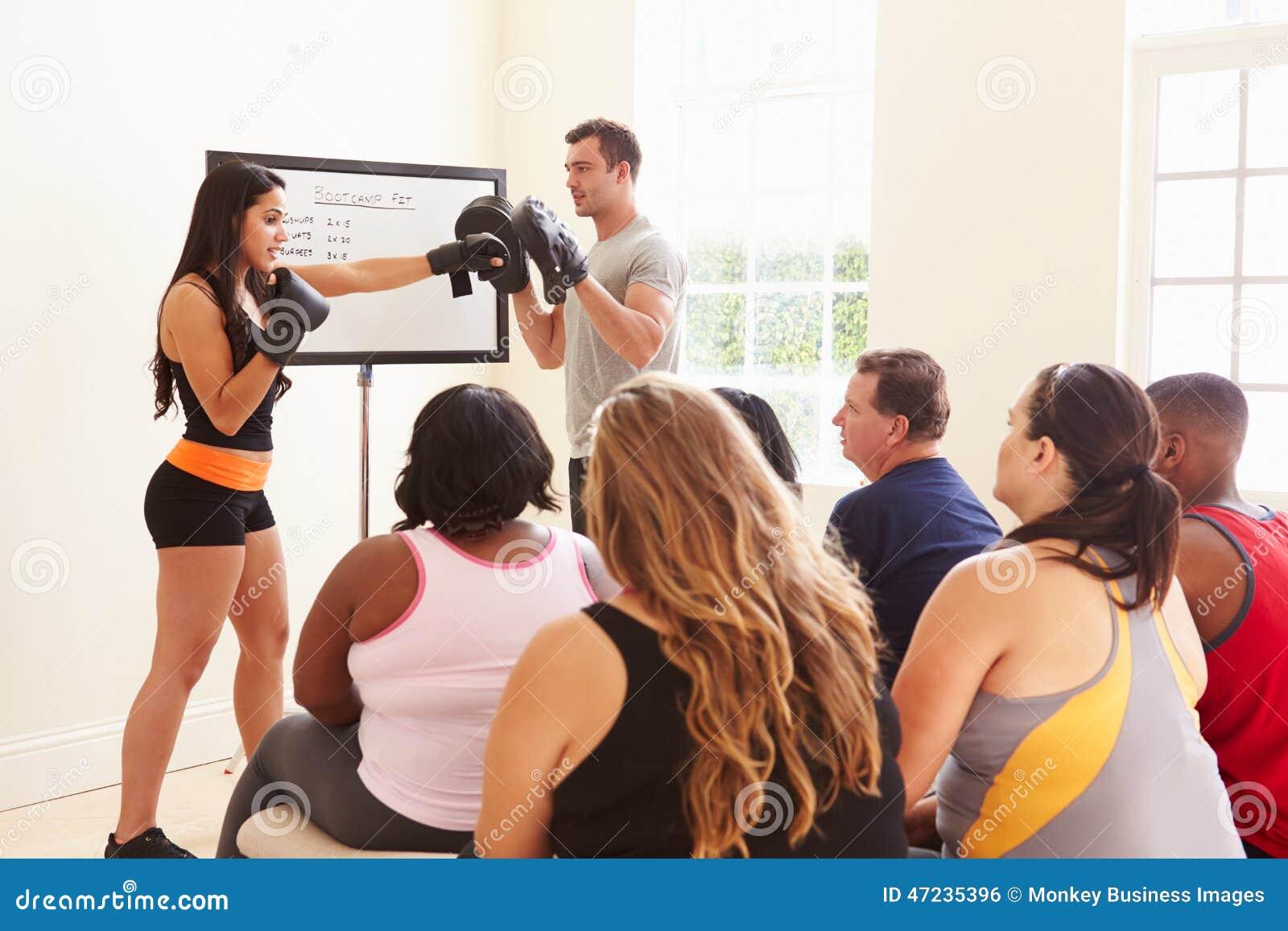 Инструктор фитнеса адресуя полные людей на клубе диеты