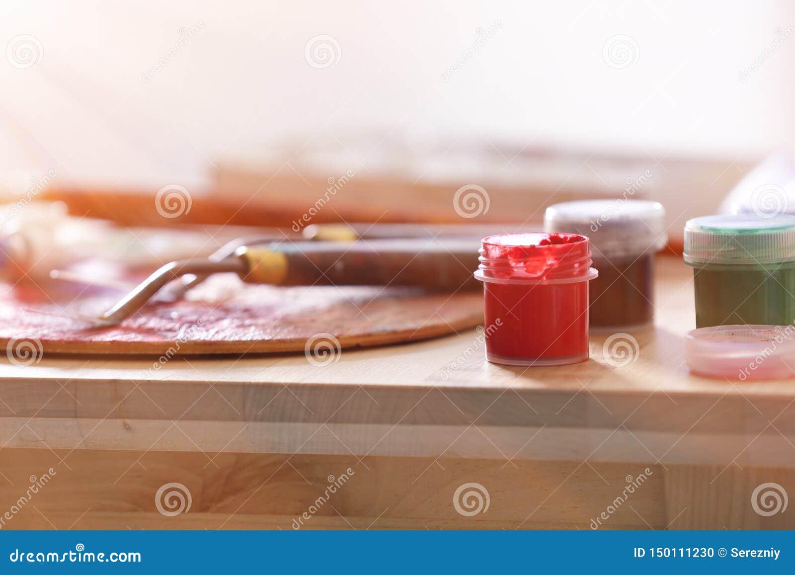 Инструменты и краски профессионального художника на деревянном столе, крупном плане