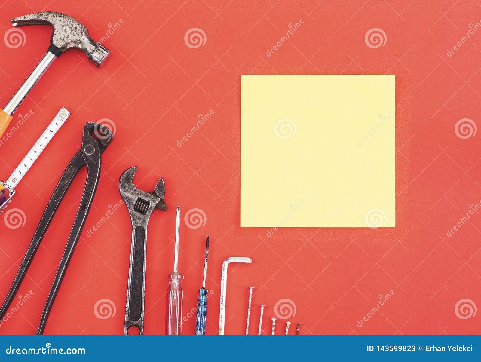 Инструменты на работниках джинсовой ткани, красная предпосылка конструктора инженера ключа с инструментами конструктора инженера