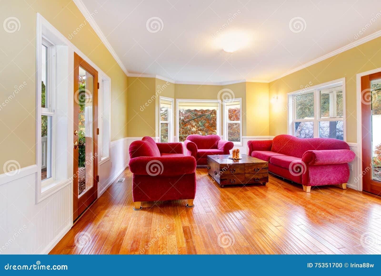 Интерьер живущей комнаты с красными софами на ферме лошади