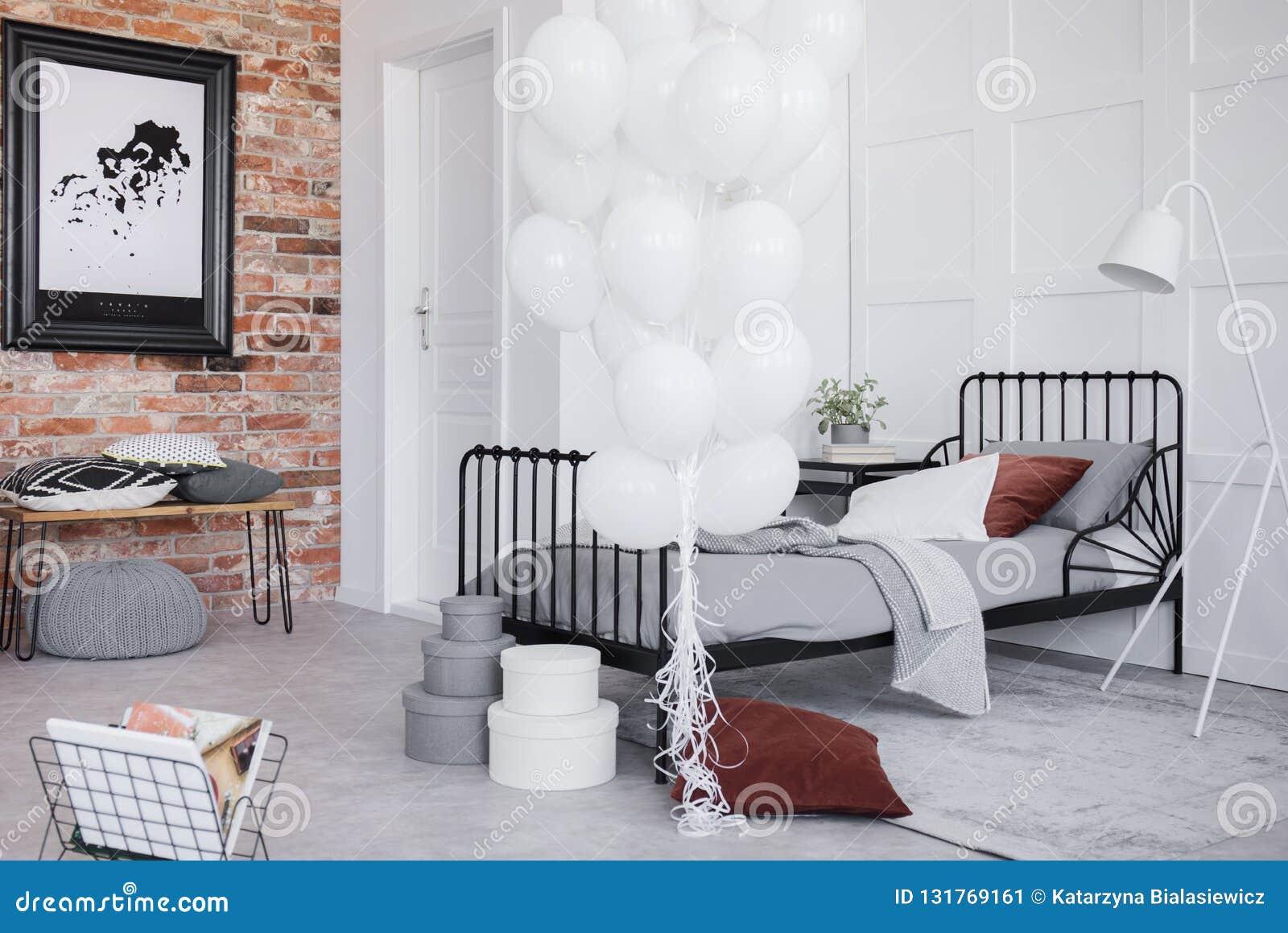 Интерьер спальни с серыми постельными принадлежностями, пук белых воздушных шаров и черная рамка на кирпичной стене, реальное фот