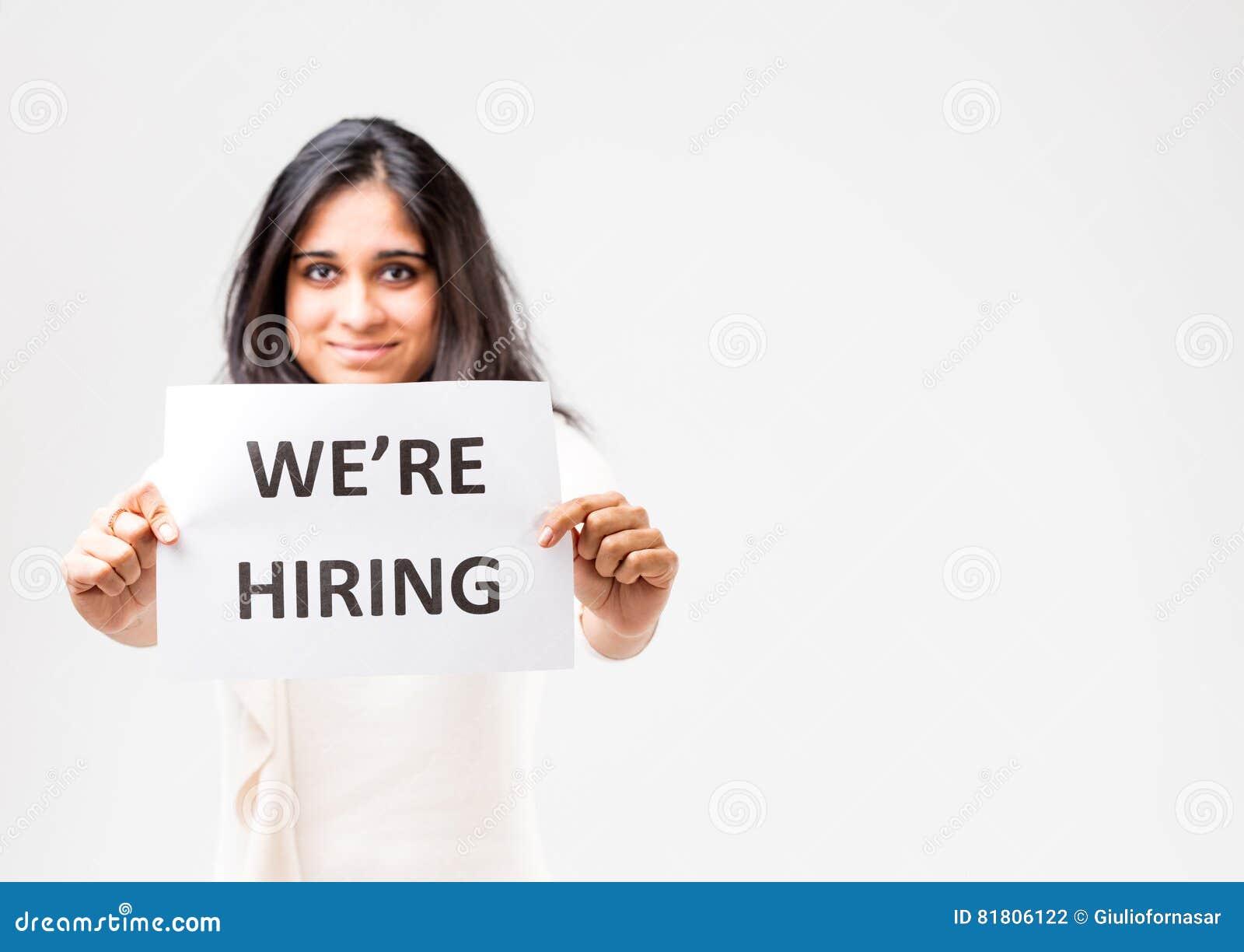 Индийская девушка держа знак рабочего места