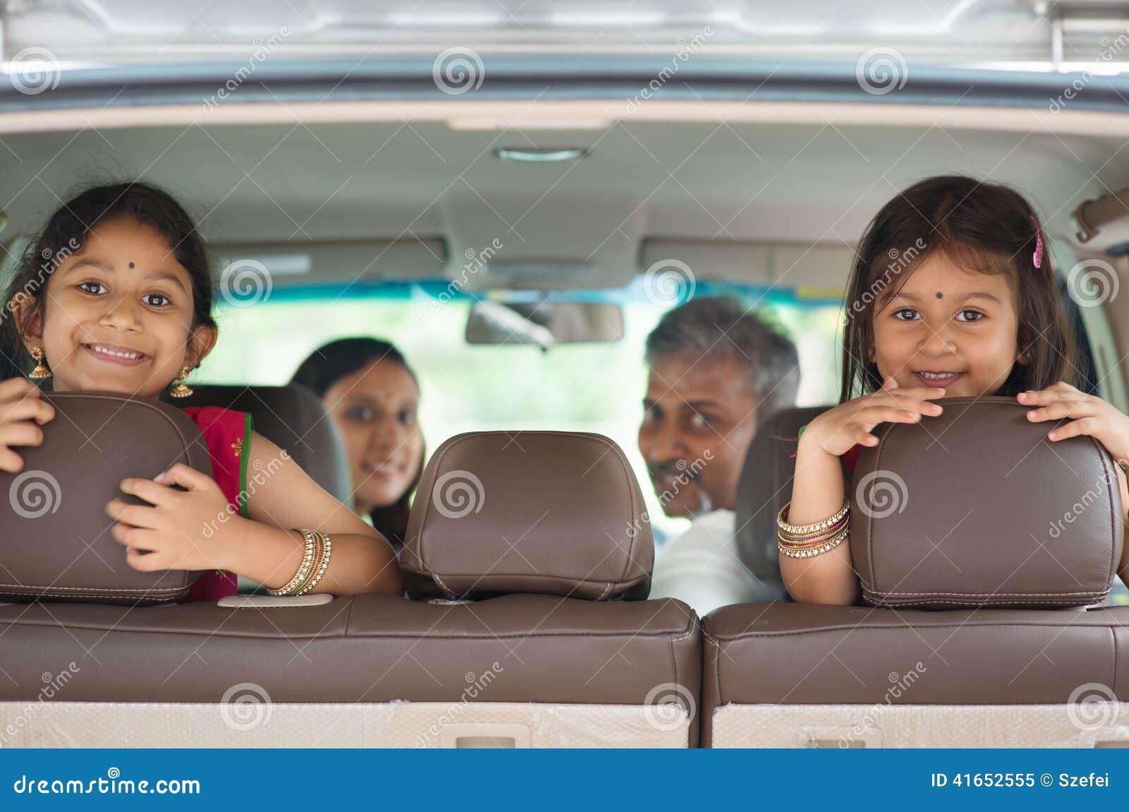 Индийская семья сидя в автомобиле