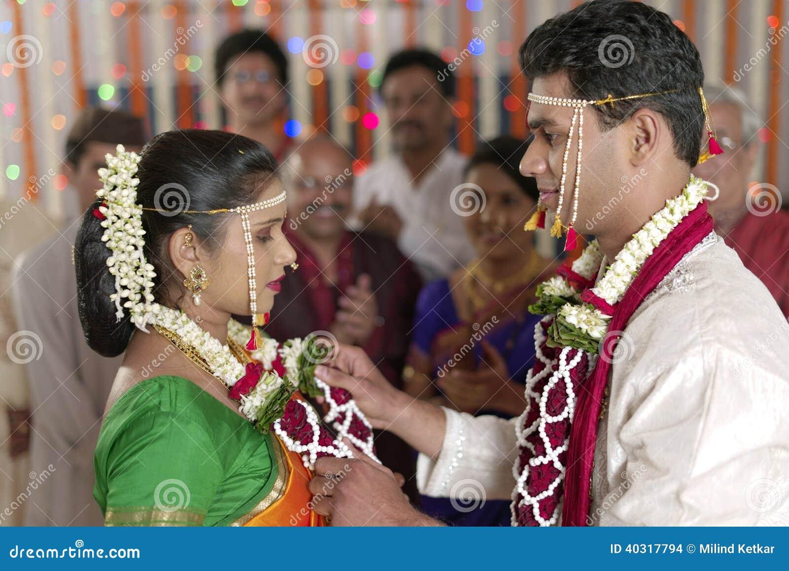 Индийский индусский Groom смотря невесту и обменивая гирлянду в свадьбе махарастры