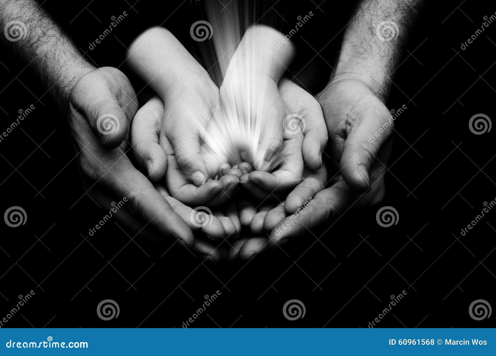 Искра надежды в ребенке вручает wh держа предпосылкой темноты handson родителей Свет веры