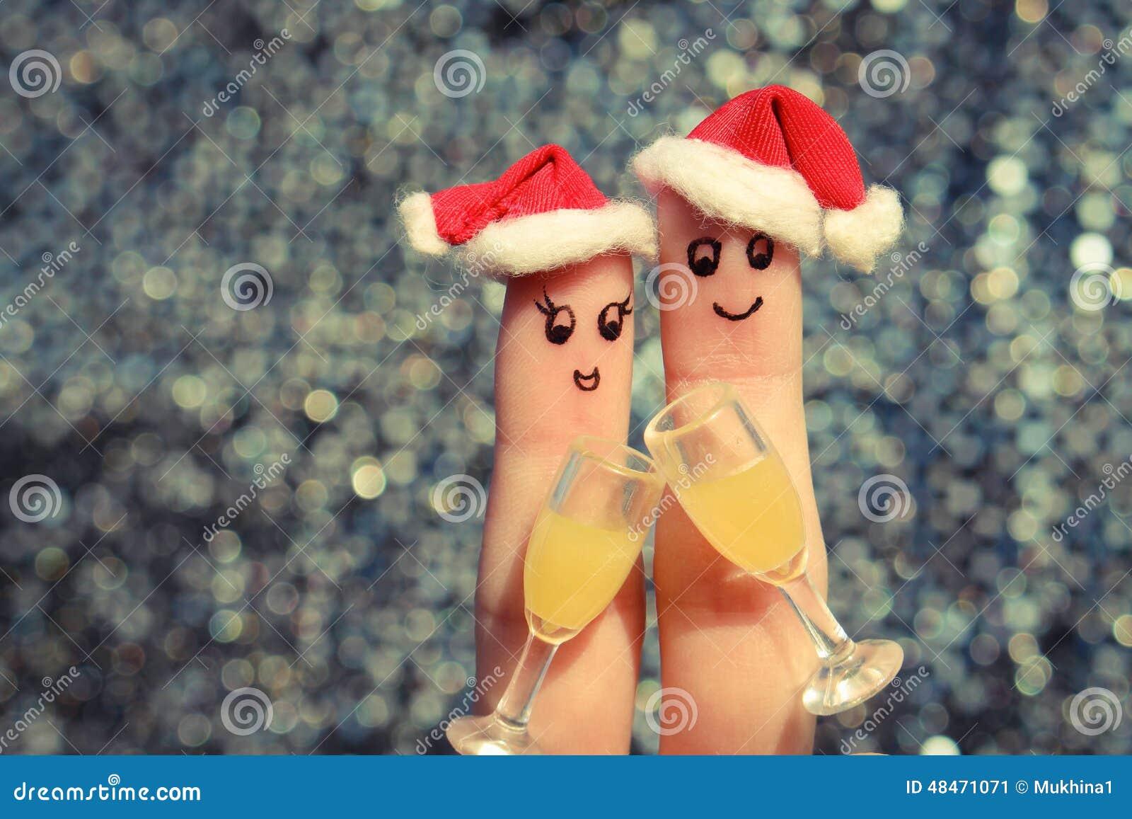 Искусство пальца счастливой пары Соедините делать хорошее приветственное восклицание в шляпах Нового Года стекла 2 шампанского