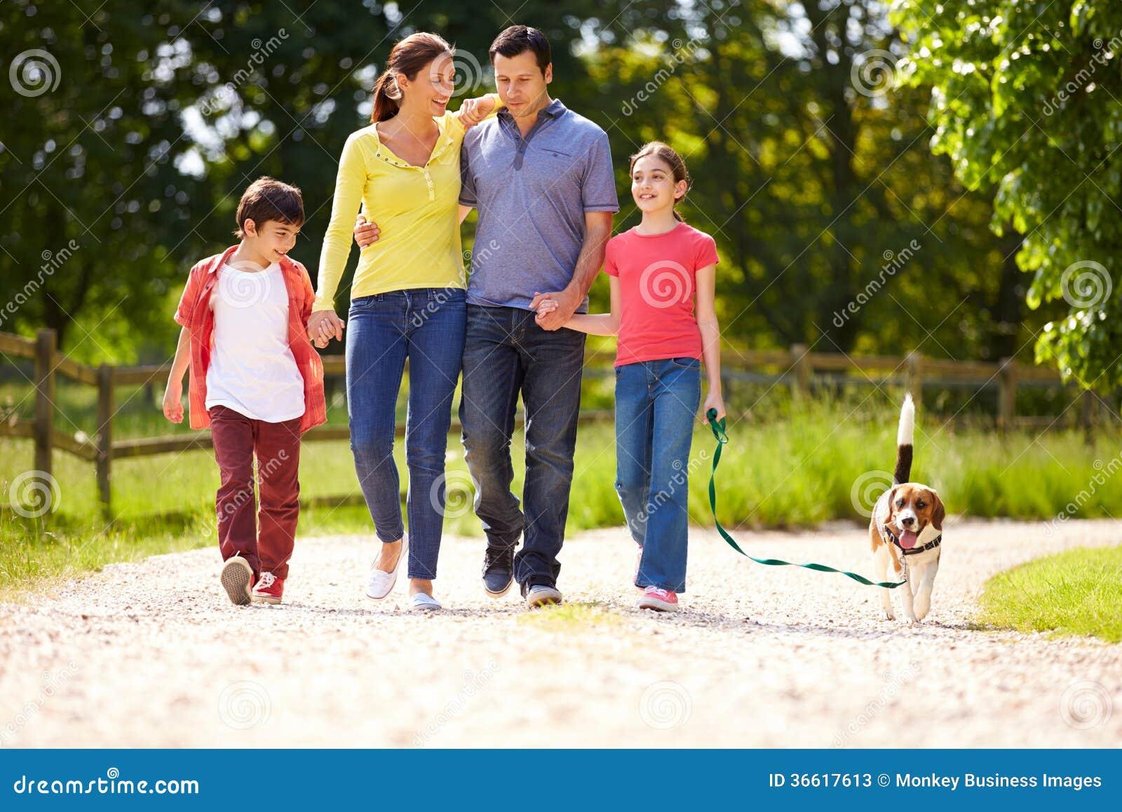 Испанская семья принимая собаку для прогулки
