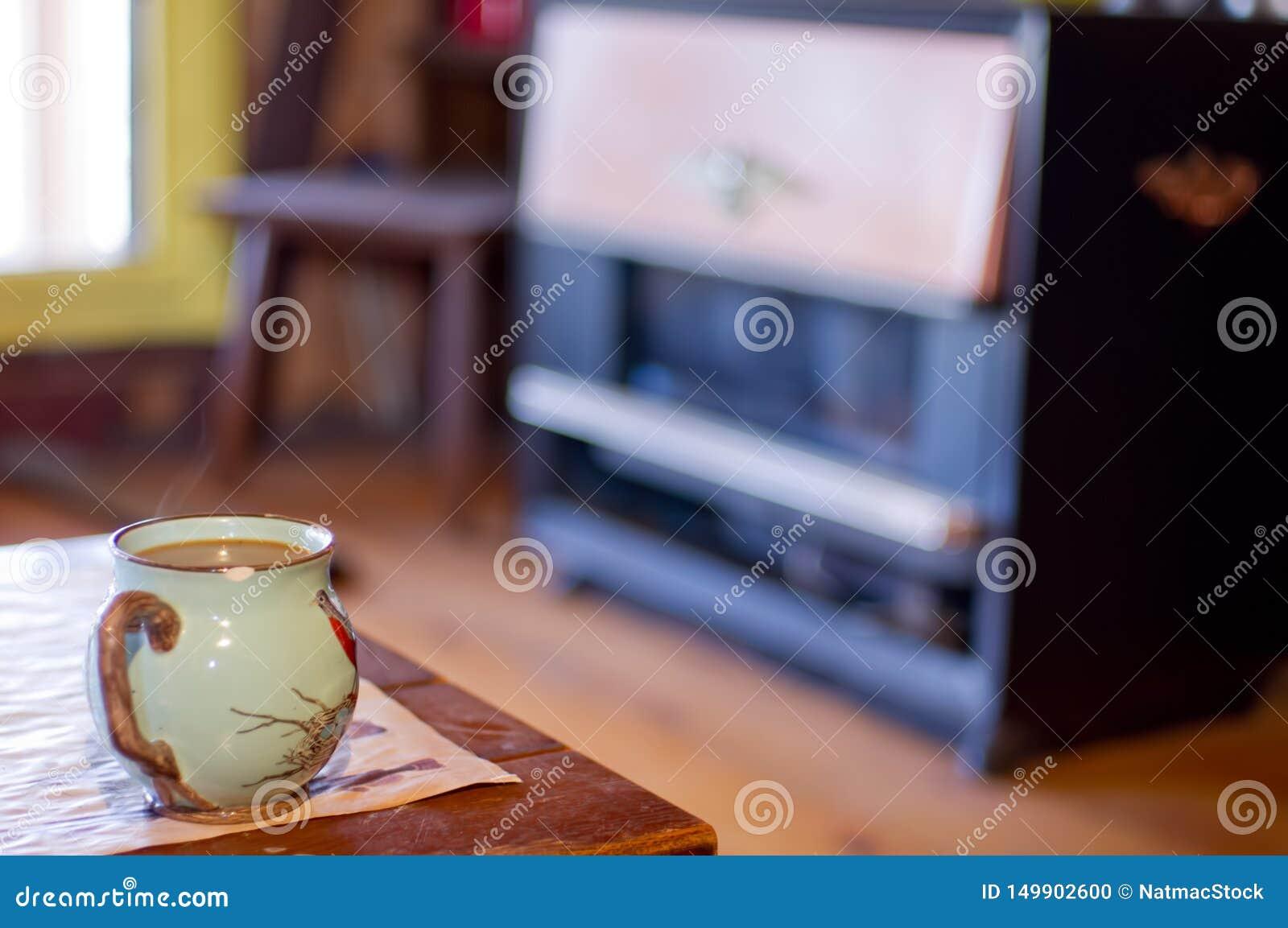 Испаряющся чашка кофе в кружке птицы с винтажным обогревателем кабины пропана/природного газа на заднем плане - принятый на дерев
