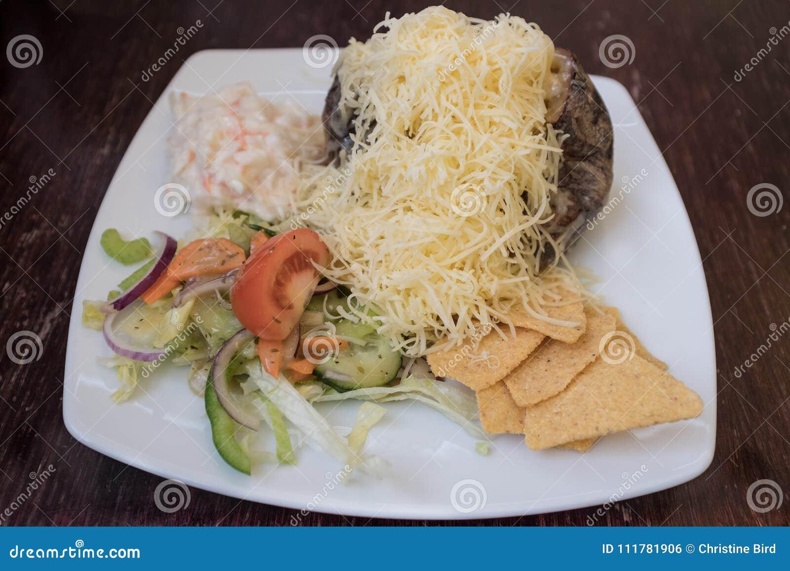 Испеченная картошка с заскрежетанным сыром, coleslaw и салатом