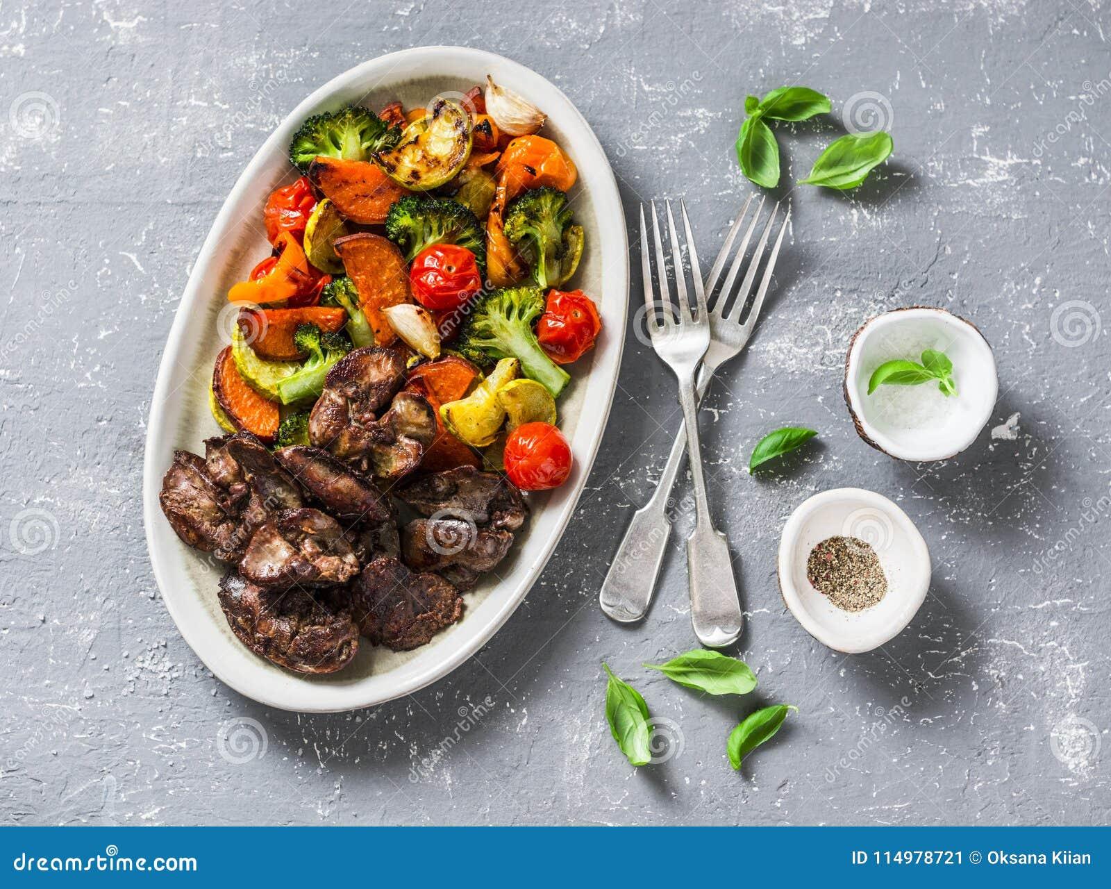 Испеченные сезонные овощи - сладкие картофели, капуста брокколи, сладостные перцы, томаты вишни, свеклы, чеснок, цукини и цыплено