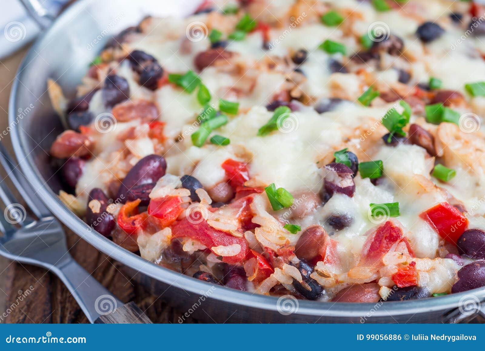 Испеченный сотейник риса с черными фасолями, фасолями пегой лошади, фасолями почки, сыром и паприкой, в блюде выпечки металла, го
