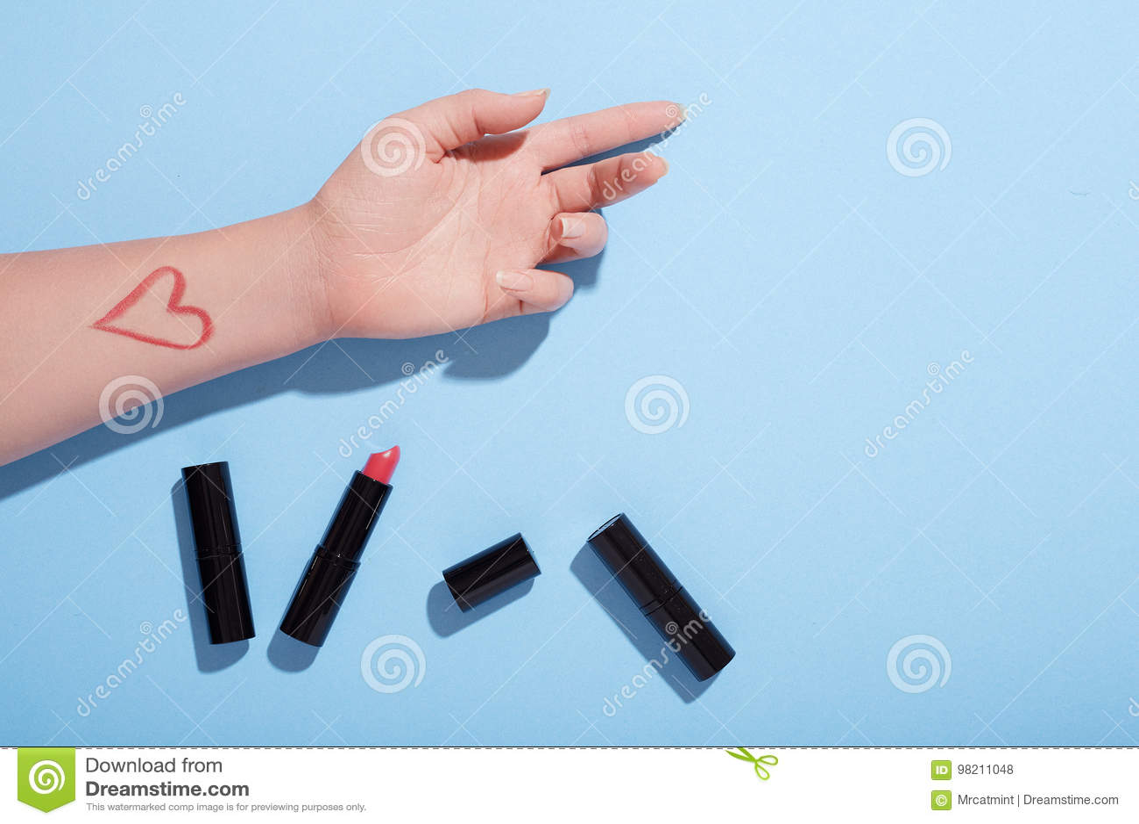 Испытание хода губной помады по рука ` s женщины, плоское положение, взгляд столешницы, голубая предпосылка