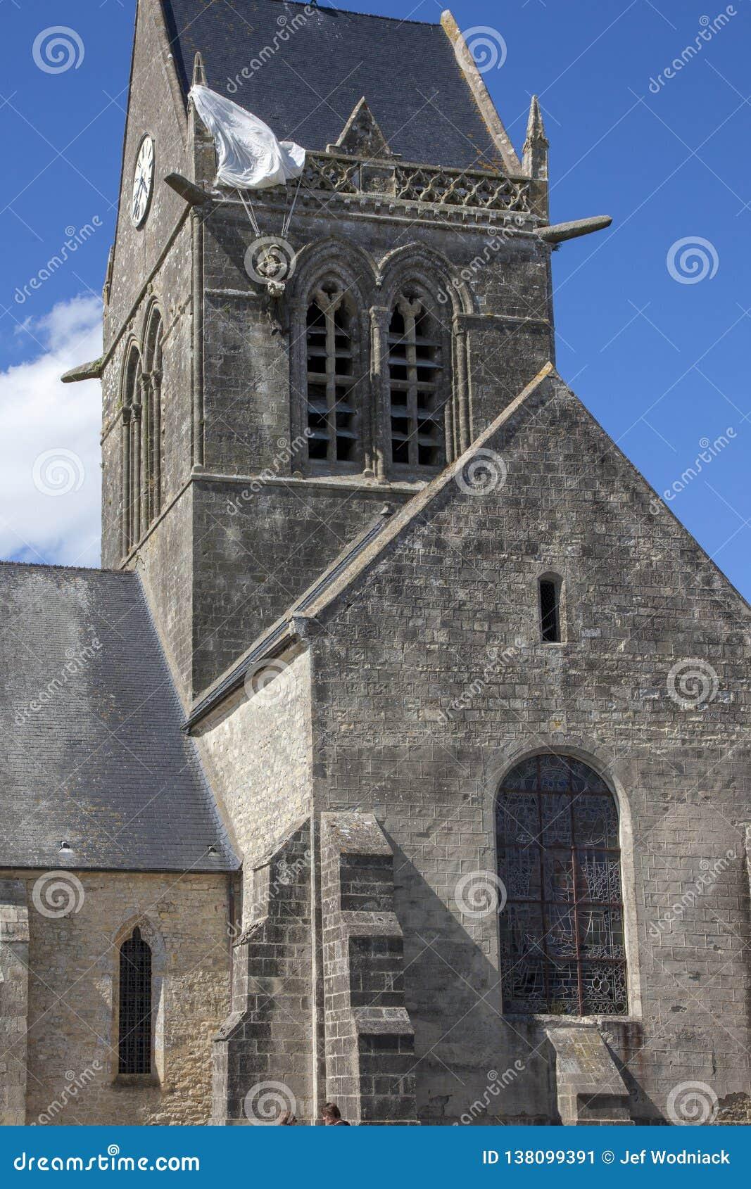 """Историческая церковь Sainte простого l """"eglise, с парашютистом вися на колокольне"""