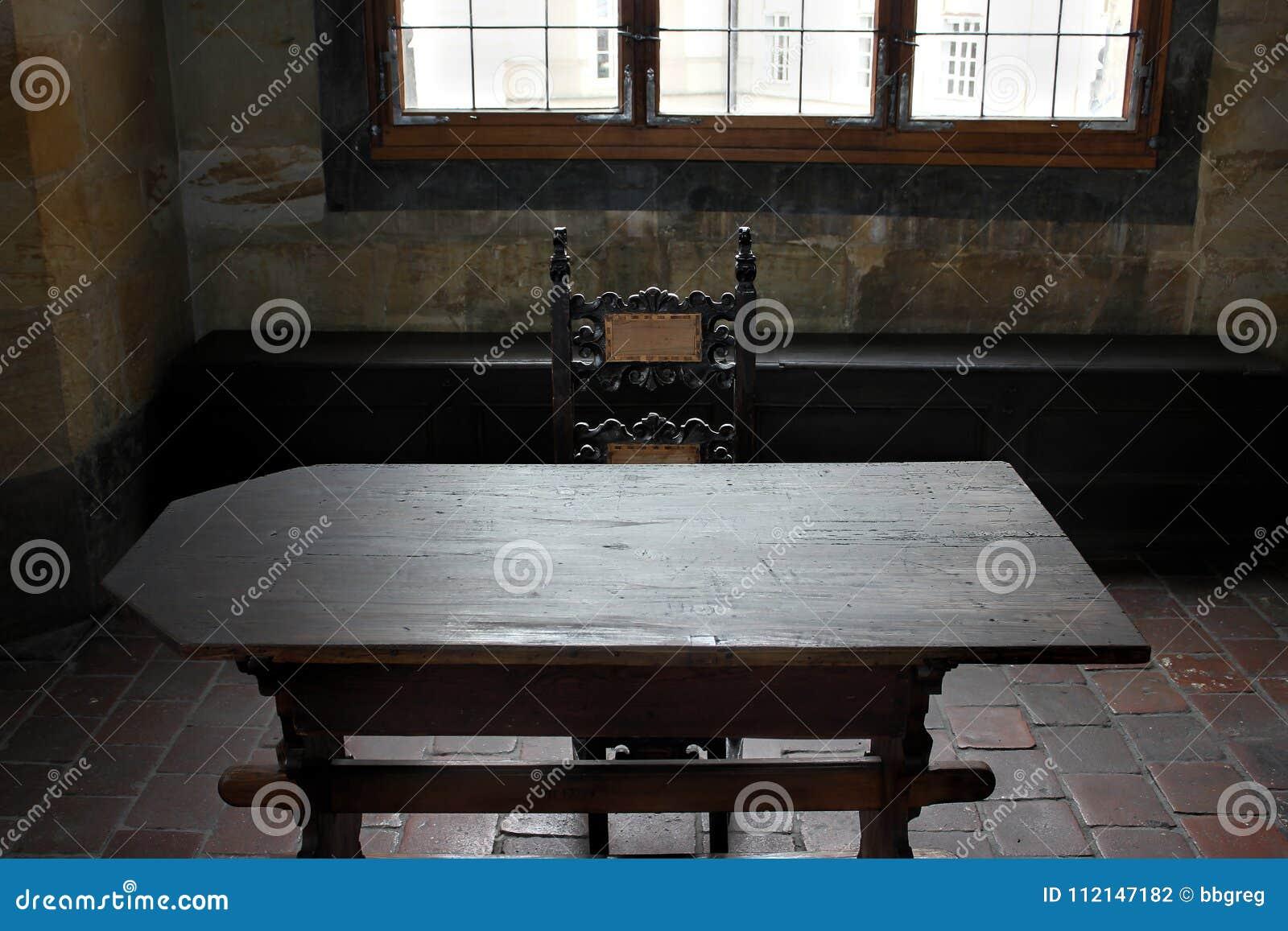 Исторический интерьер с деревянной мебелью, декоративным потолком, деревянным полом, картинами на стенах и окнами на средневеково