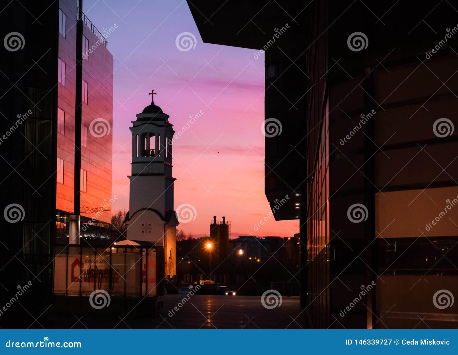 Исторический церковный колокол отражая живые цвета на заходе солнца