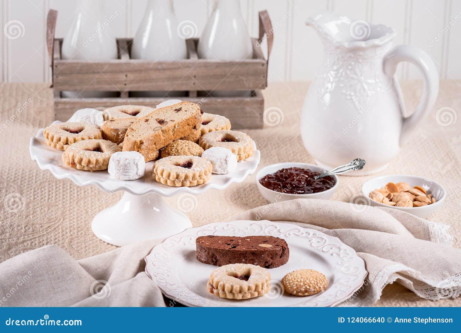 Итальянские печенья с вареньем, миндалинами, бутылками молока и кувшином на беже покрасили скатерть