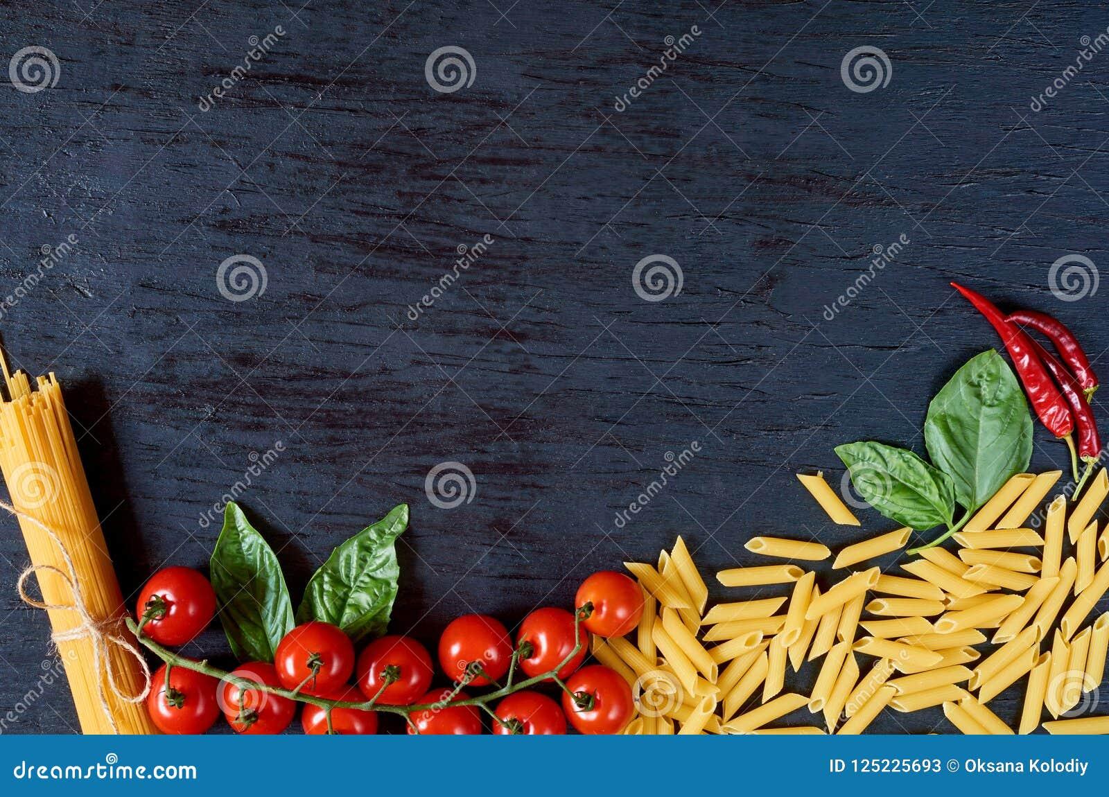 Итальянские традиционные еда, специи и ингридиенты для варить: листья базилика, томаты вишни, перец chili и различные макаронные