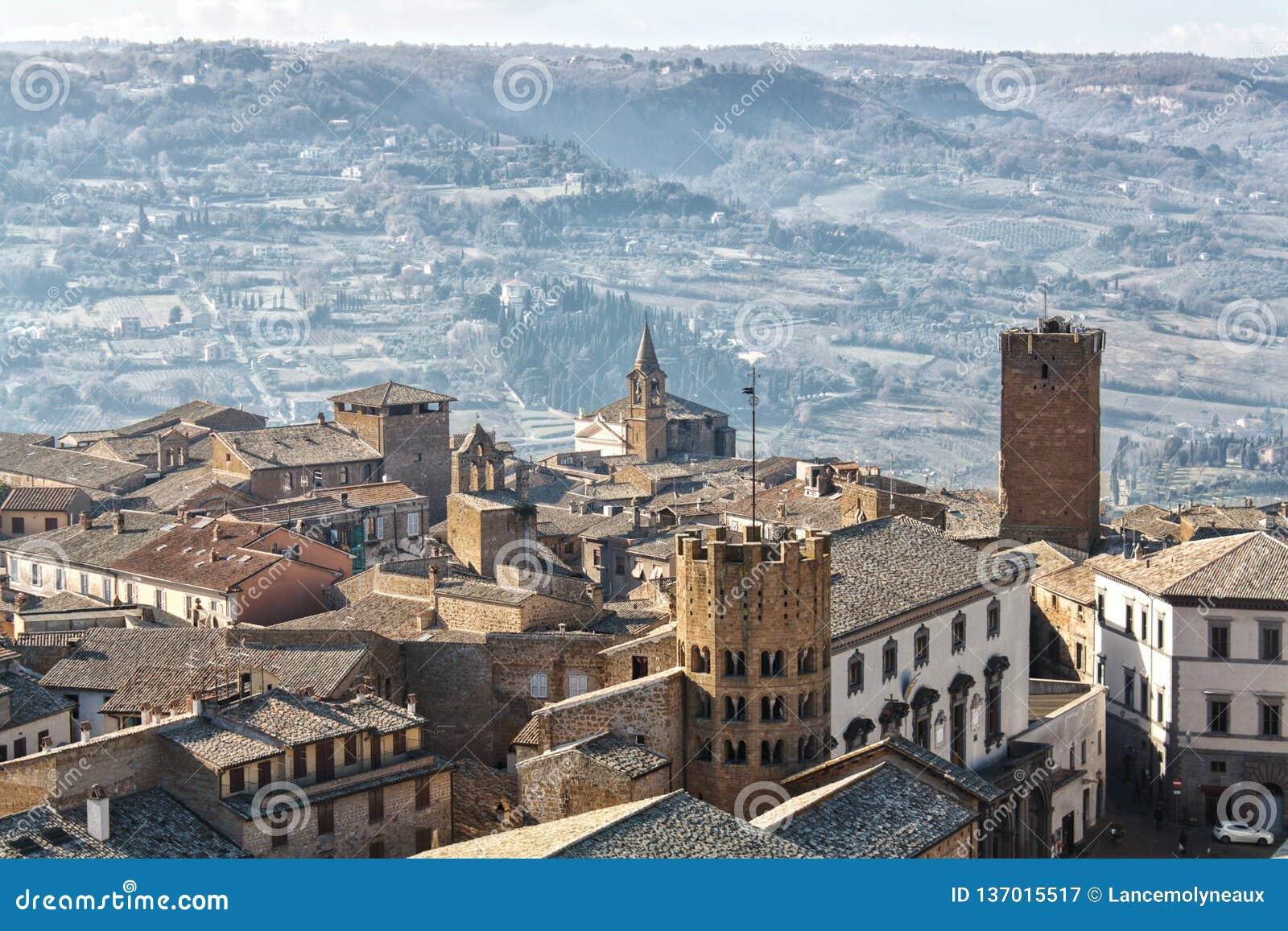 Итальянский городок вершины холма сидит высоко над сельской местностью в расстоянии