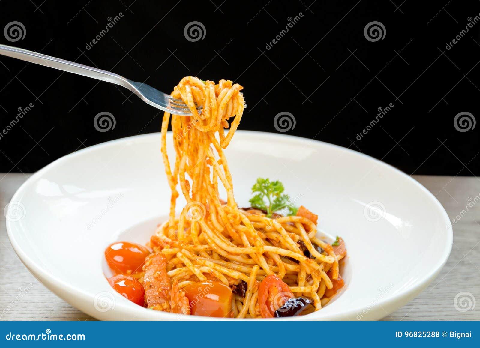 Итальянская женщина еды есть спагетти с вилкой в белой плите