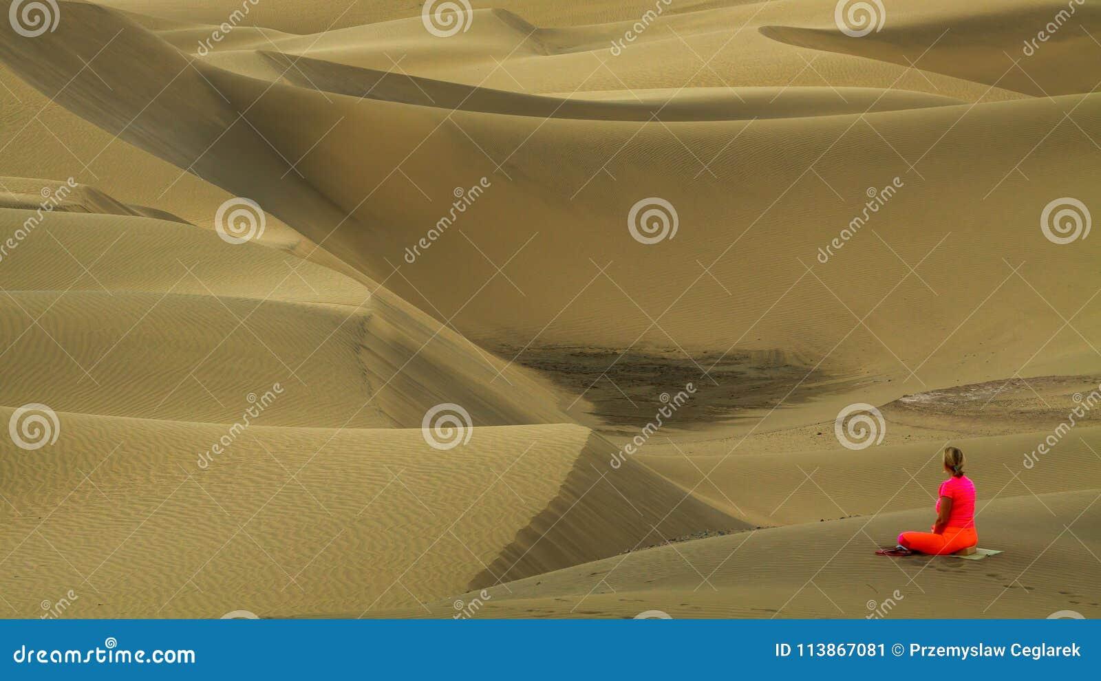 Йога женщины практикуя в песчанных дюнах