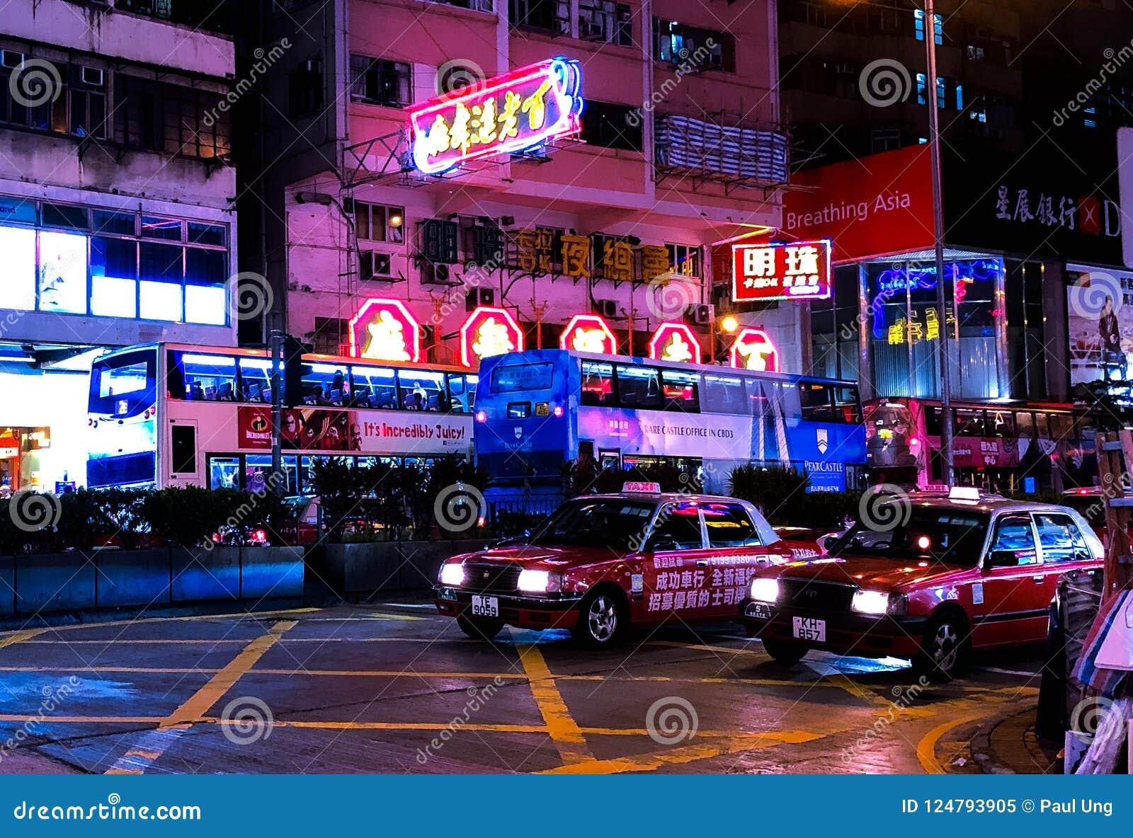Кабина Гонконга на блеске ночи с неонами