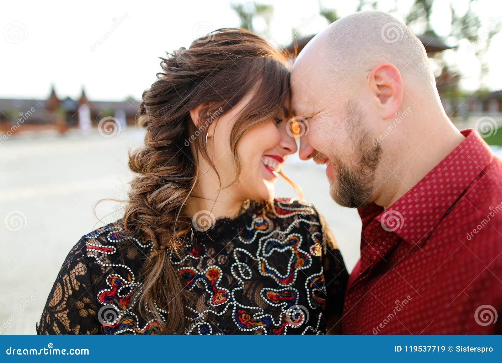 Кавказский супруг нося красную рубашку и обнимая жену