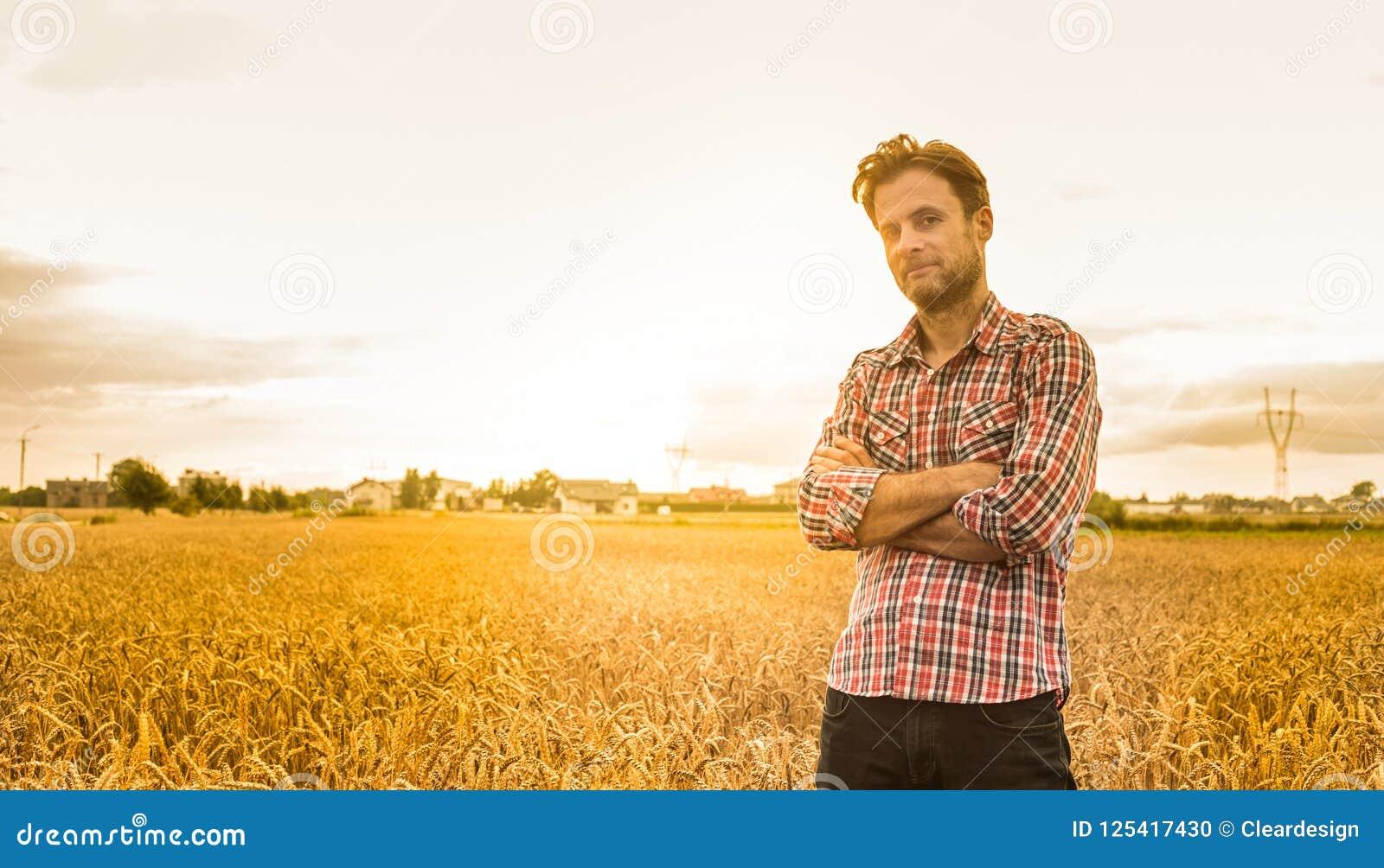 Кавказский фермер в рубашке шотландки и пшеничном поле - земледелии