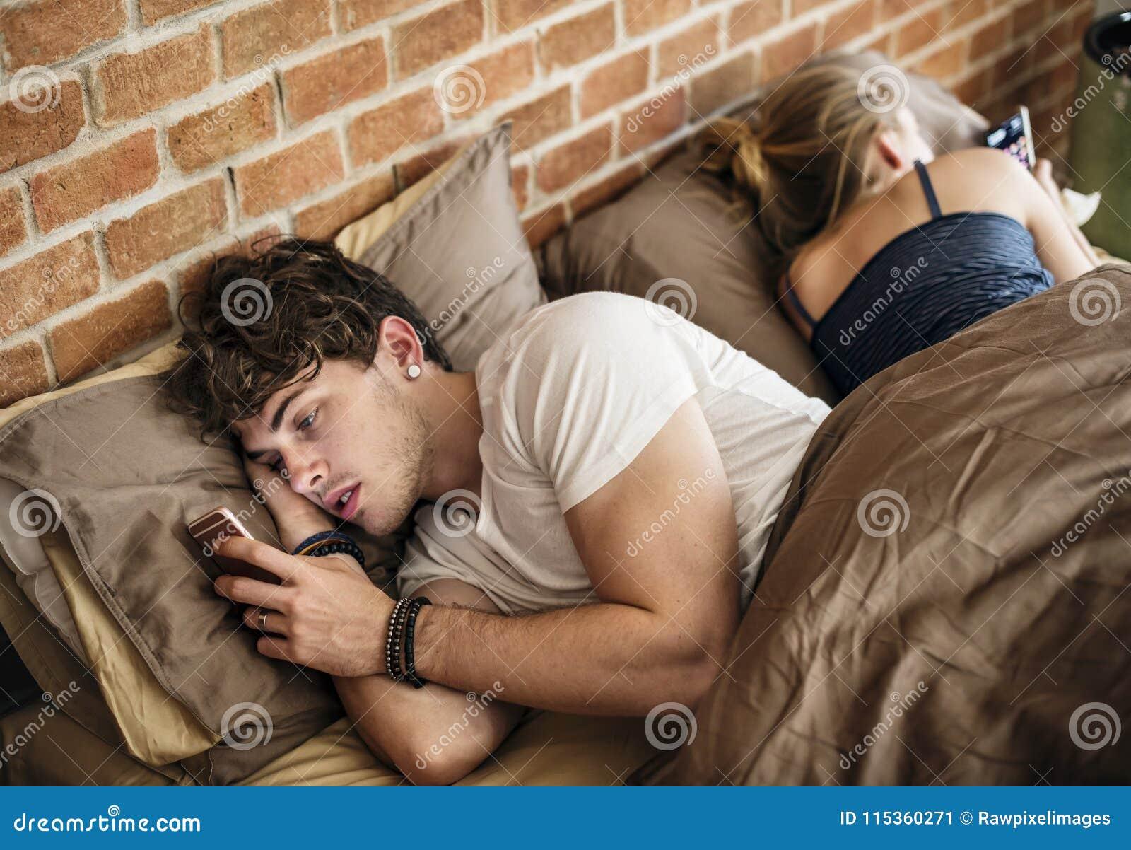 Кавказский человек используя мобильный телефон в кровати