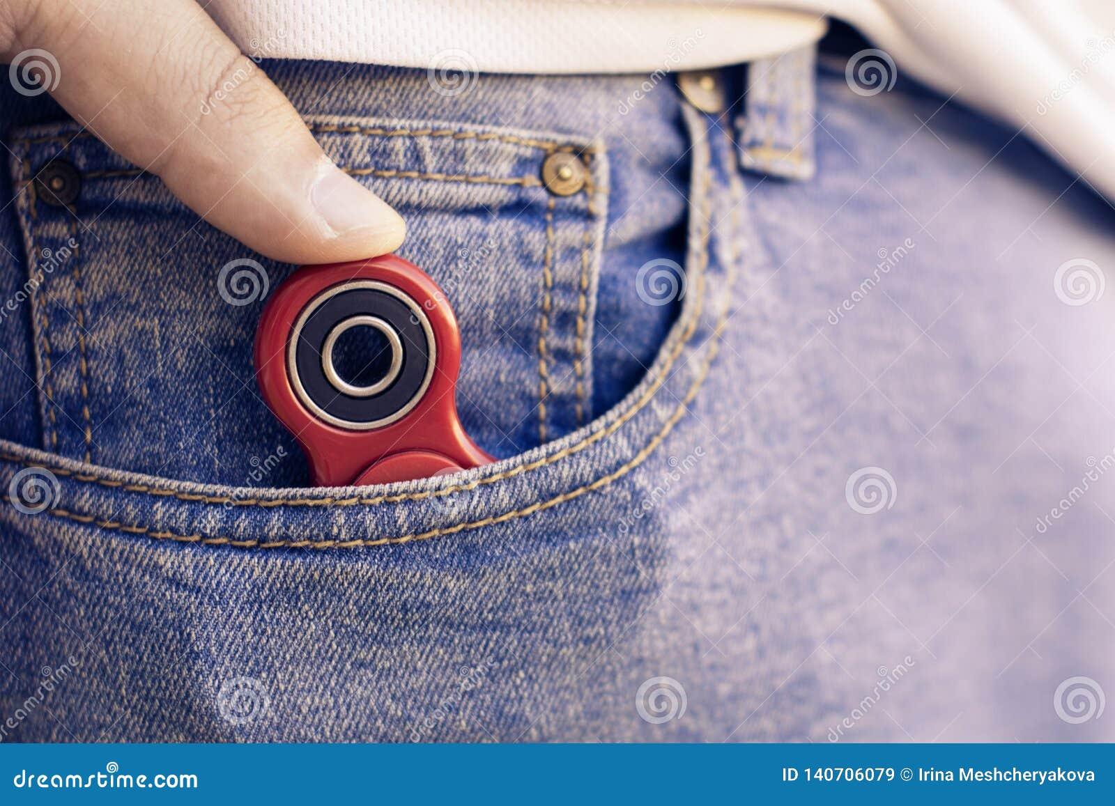 Кавказский человек прячет его красный обтекатель втулки непоседы пальца на кармане джинсов Популярное устройство обтекателя втулк