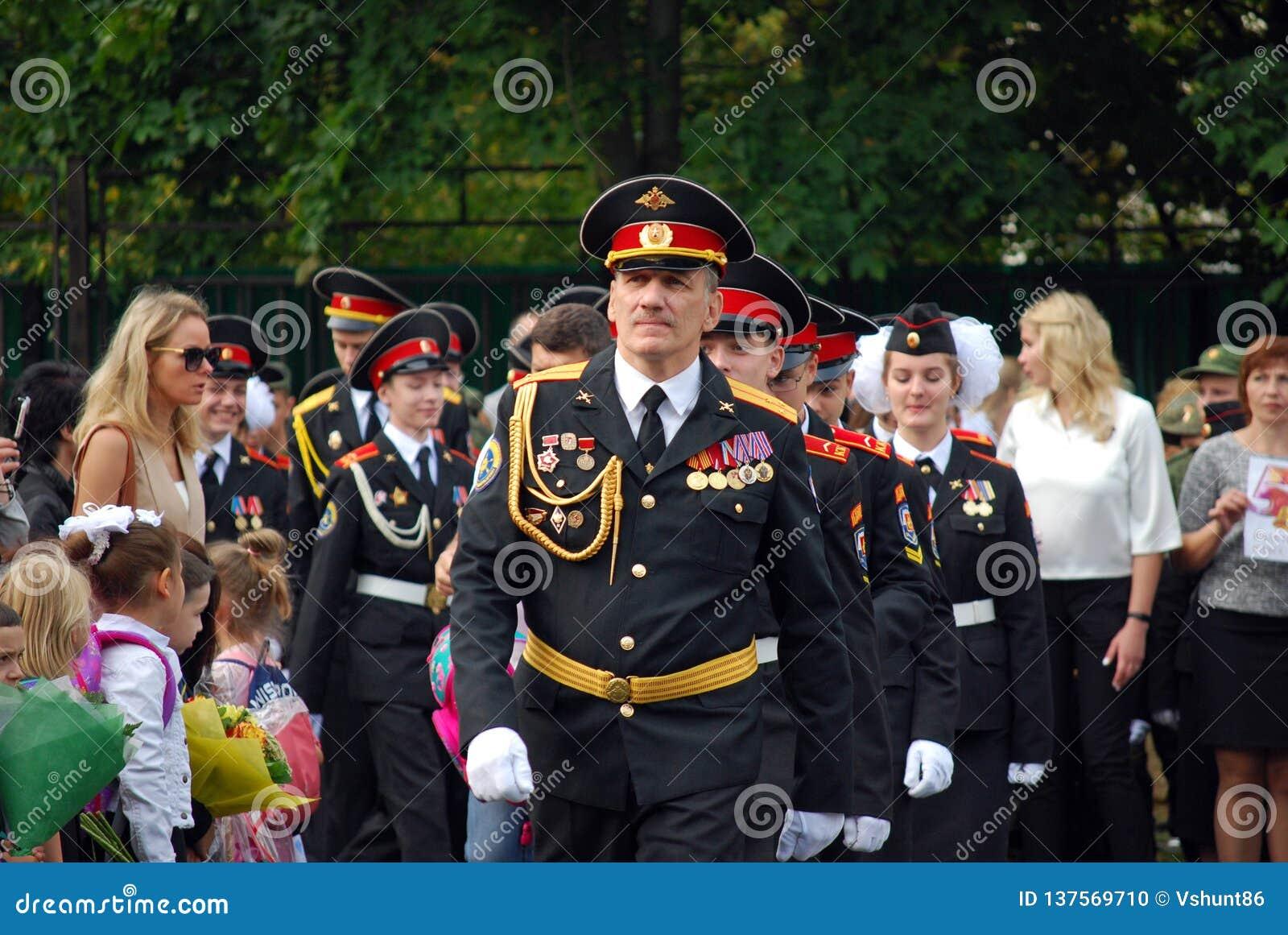 Кадеты маршируют со знаменем на правителе утра перед школой на плаце Студенты школы