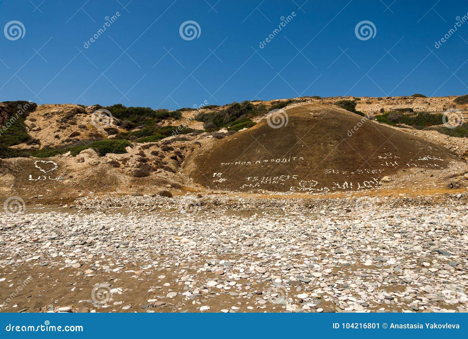 Каменные inscribed сочинительства и сердца влюбленности на холме на утесе Афродиты приставают к берегу в Кипре