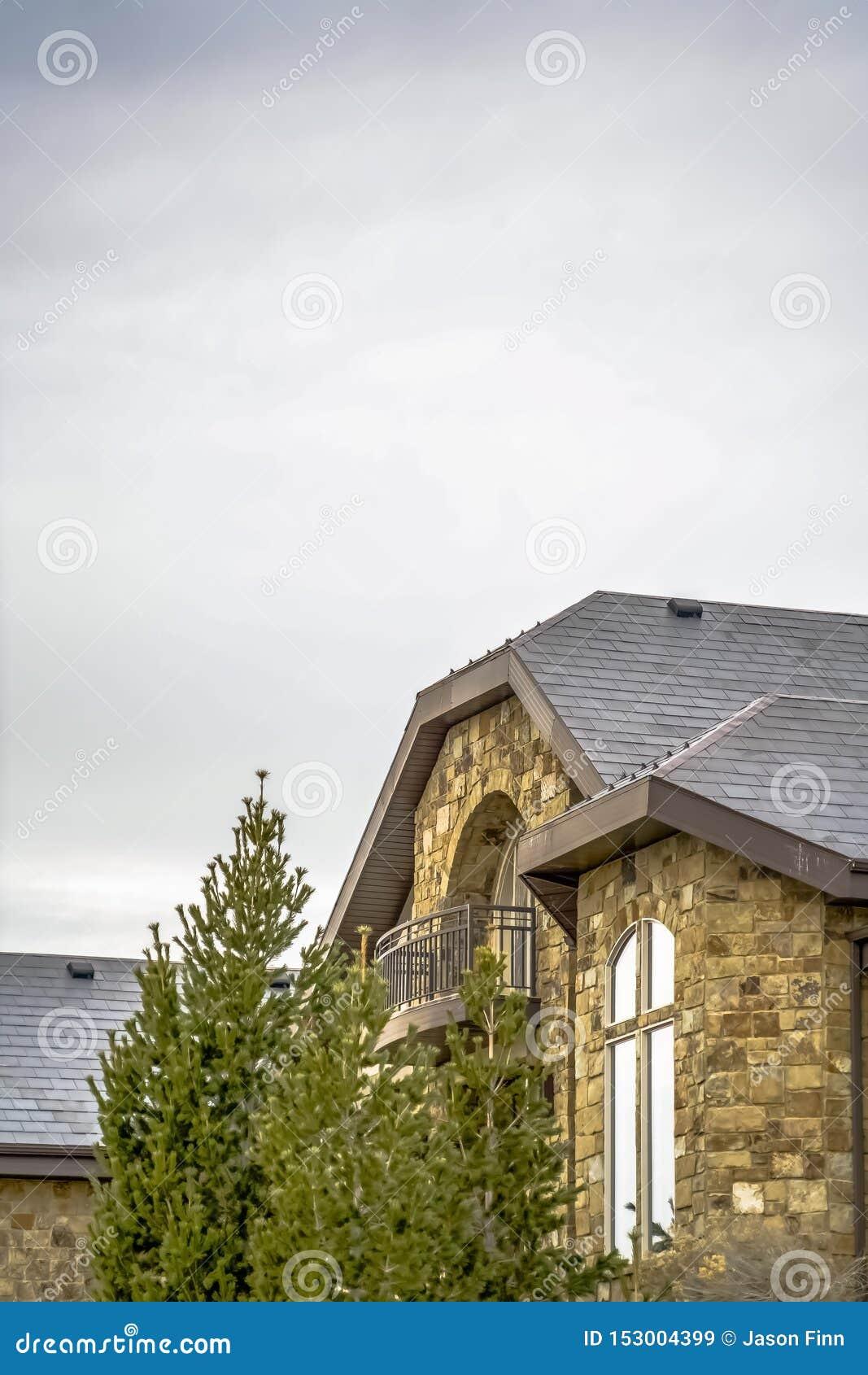 Каменный дом с балконом полкруга и квартальный круг с выдвинутым окном ноги