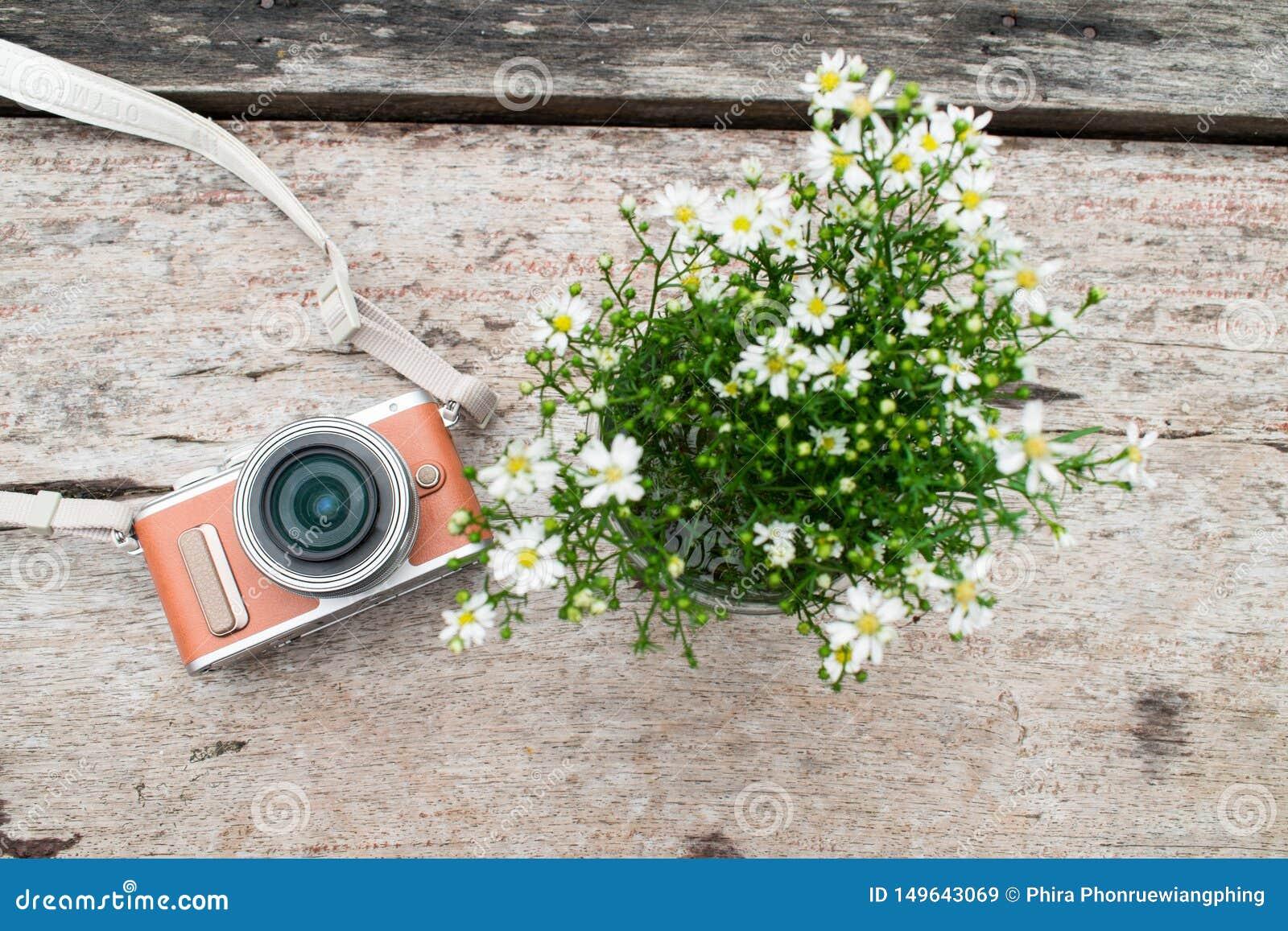 Камера с вазой белого цветка на старом коричневом деревянном столе r