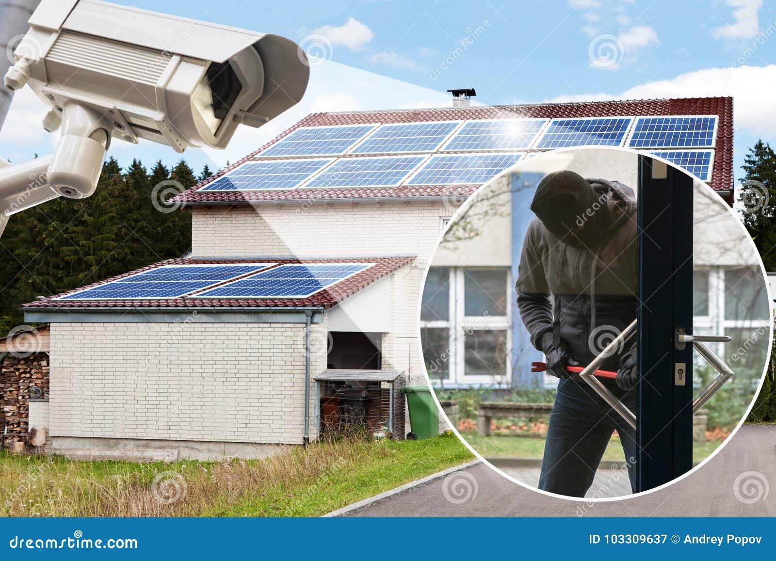 Камера CCTV показывая взломщика пробуя раскрыть дверь
