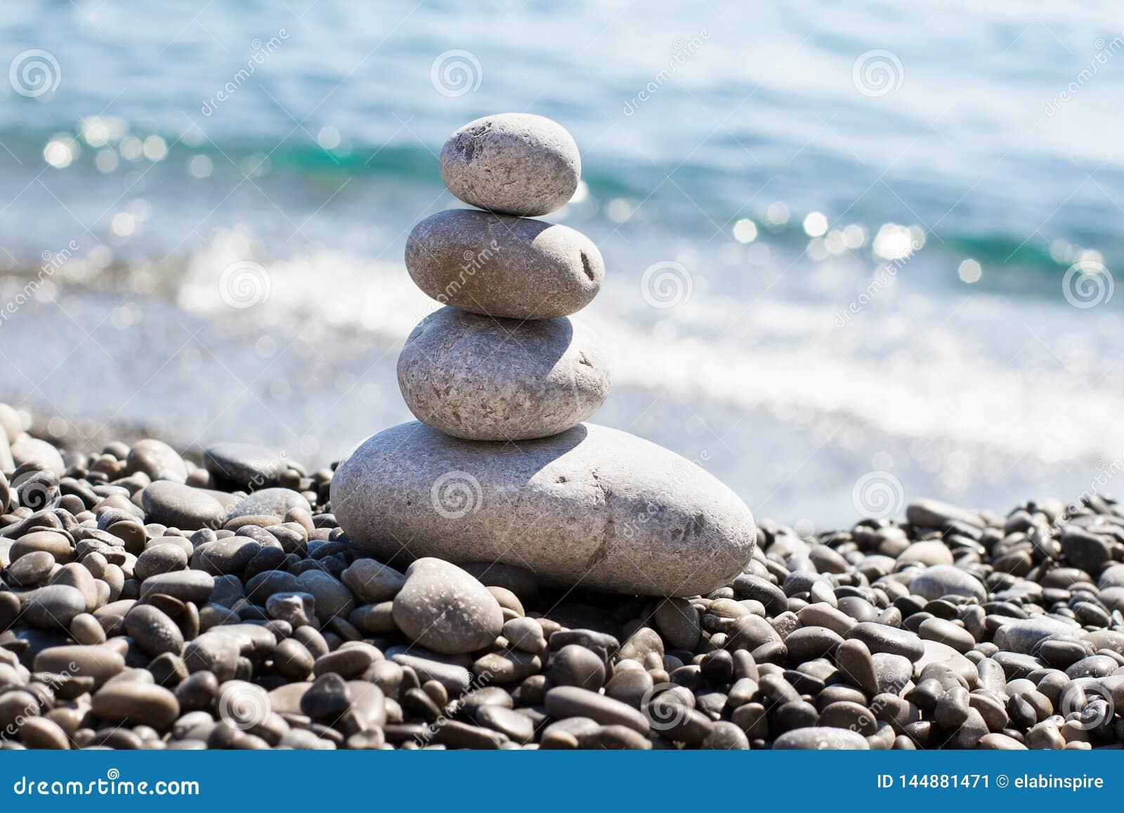 Камешки камней моря дзэна штабелированные в пирамиде на морском побер