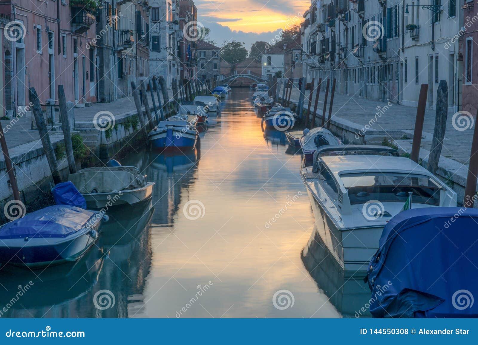 Канал Венеции с припаркованными шлюпками