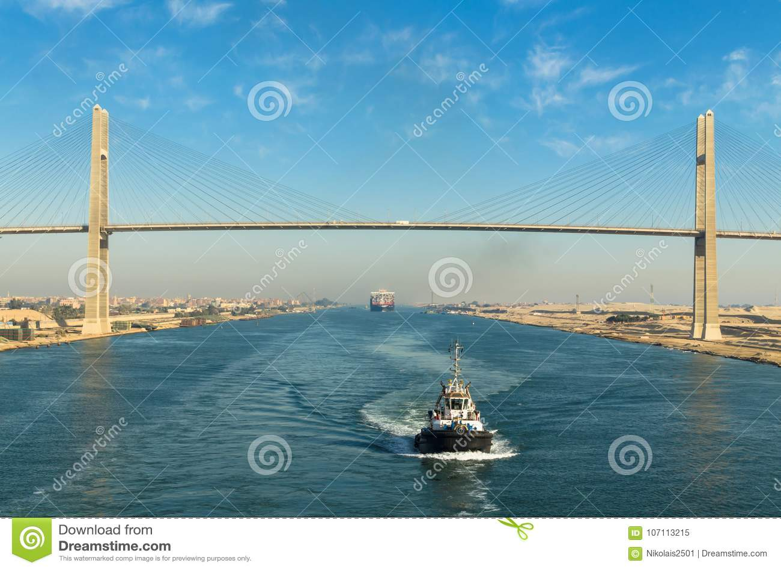 Канал Суэца, Египет, 2017: Грузите обоз ` s пропуская через канал Суэца, на заднем плане - мост канала Суэца