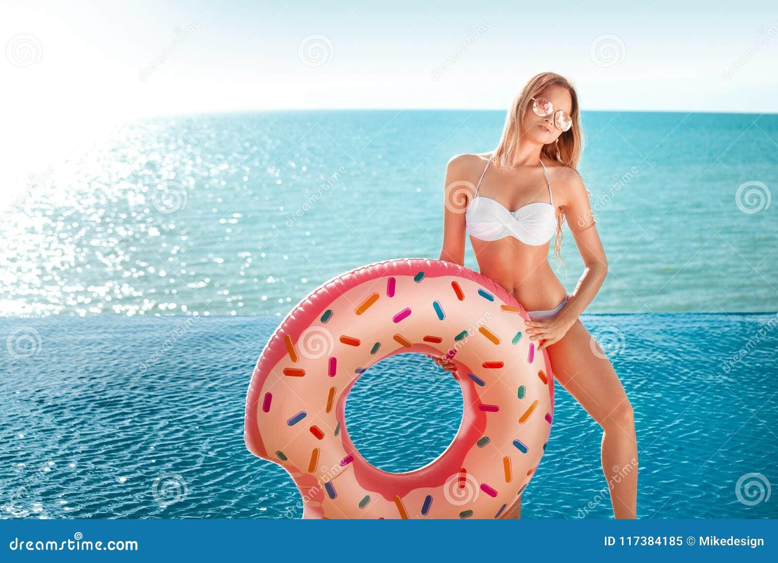каникула территории лета katya krasnodar Наслаждаться женщиной suntan в белом бикини с тюфяком донута около океана
