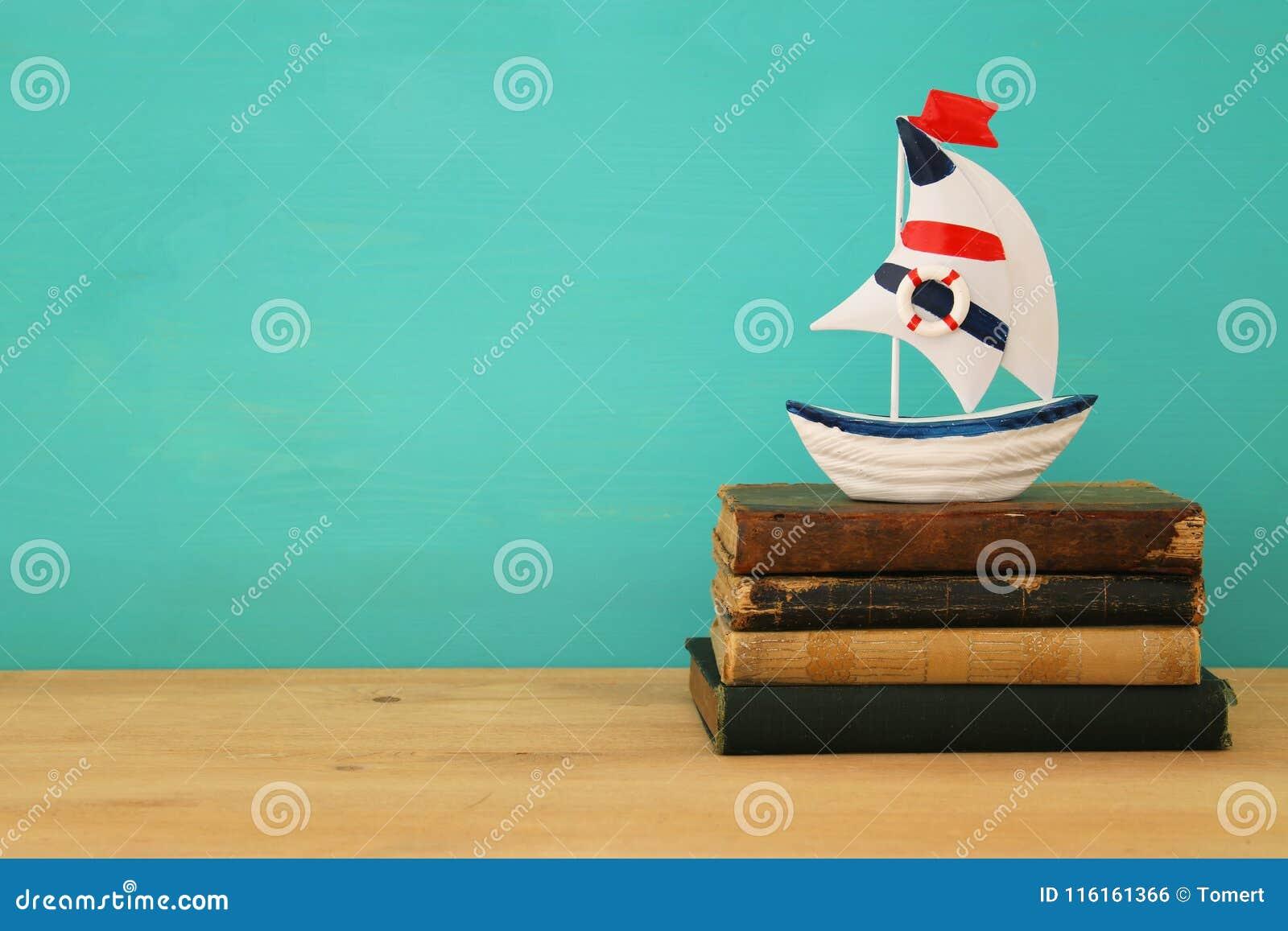 Каникулы и лето отображают с книгами шлюпки и антиквариата над деревянным столом
