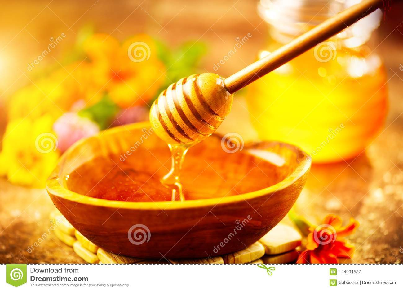 Капание меда от ковша меда в деревянном шаре Здоровый органический толстый мед лить от деревянной ложки меда