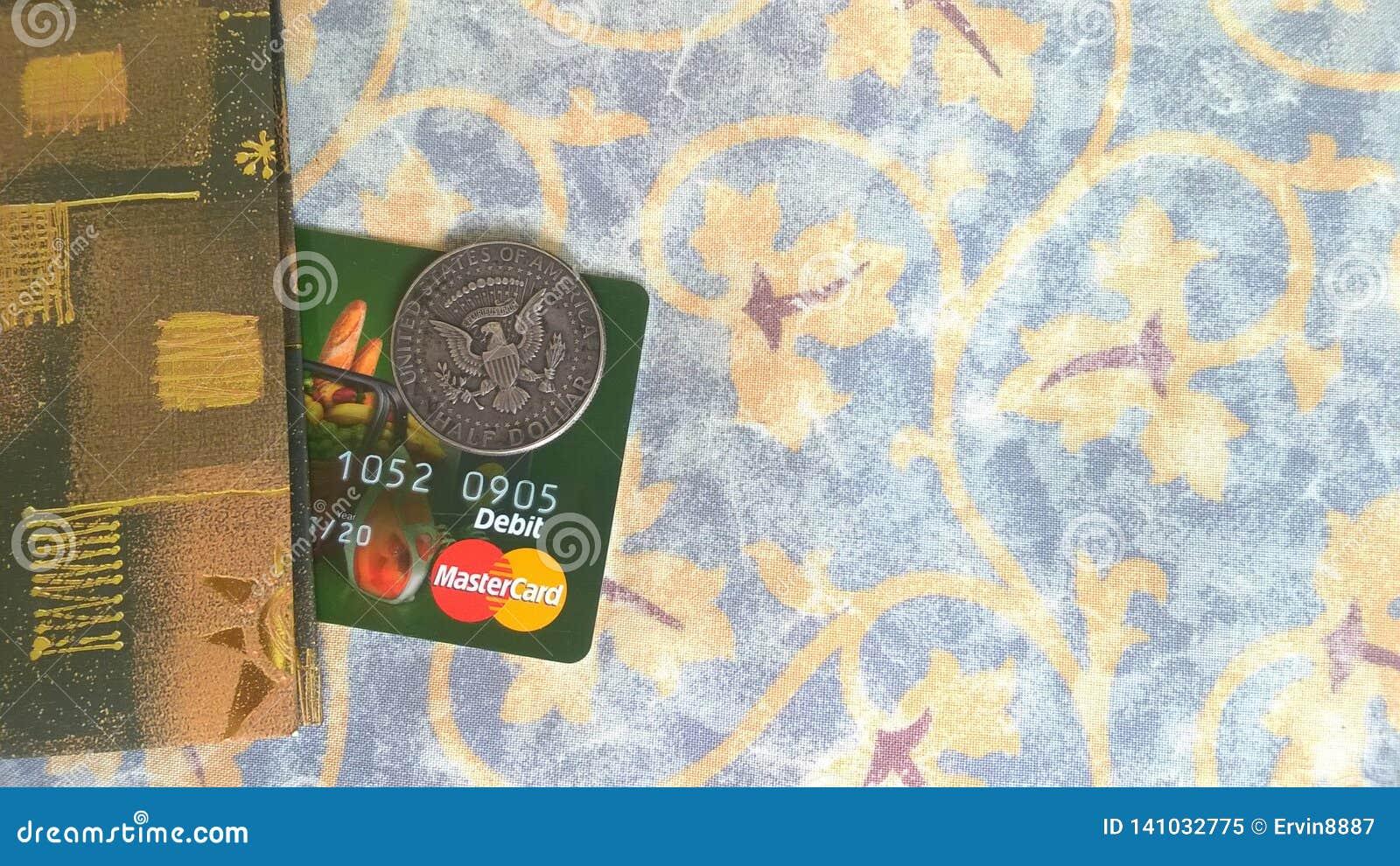 Карта банка Mastercard и монетка полдоллара