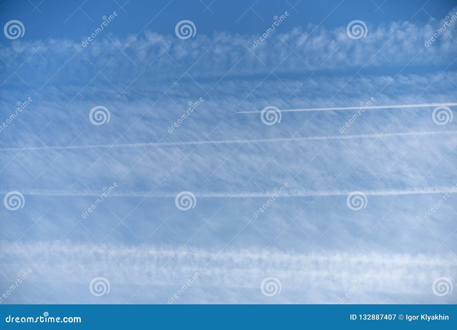 Картина следов самолета сконденсированного одина другого воздуха оплетая против голубого неба