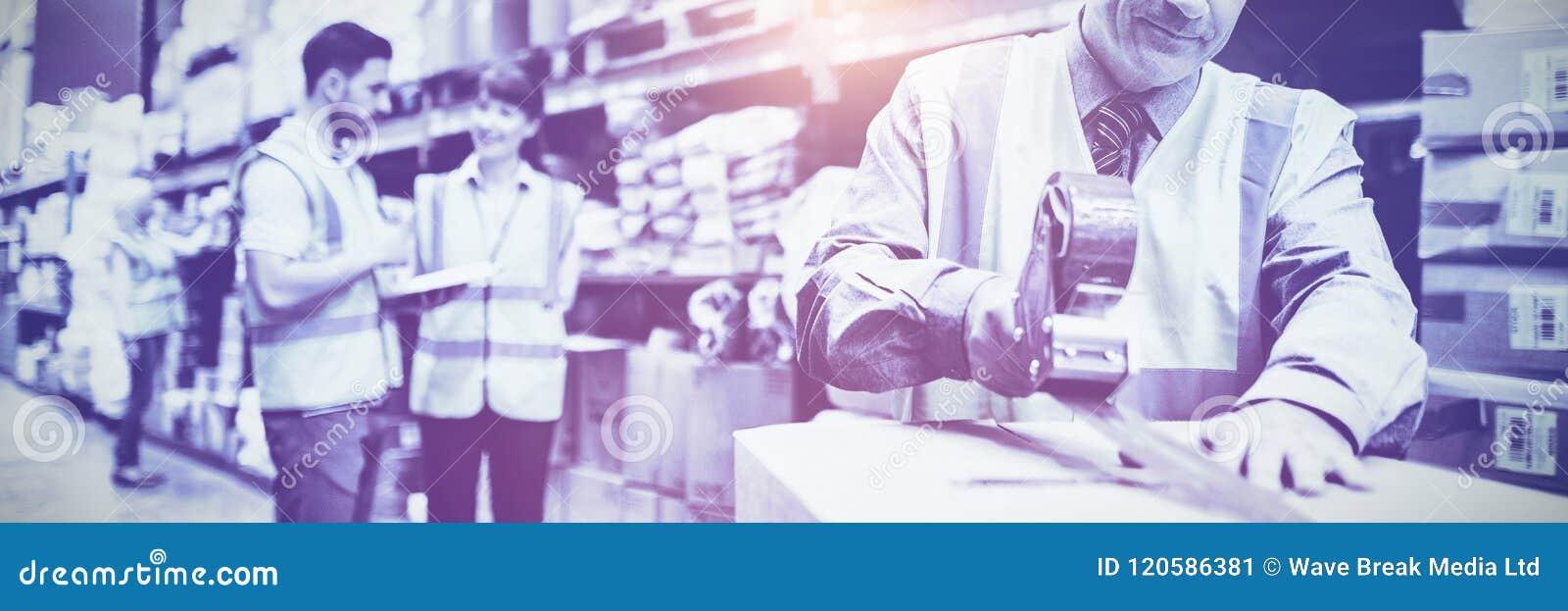 Картонные коробки запечатывания работника склада для грузить